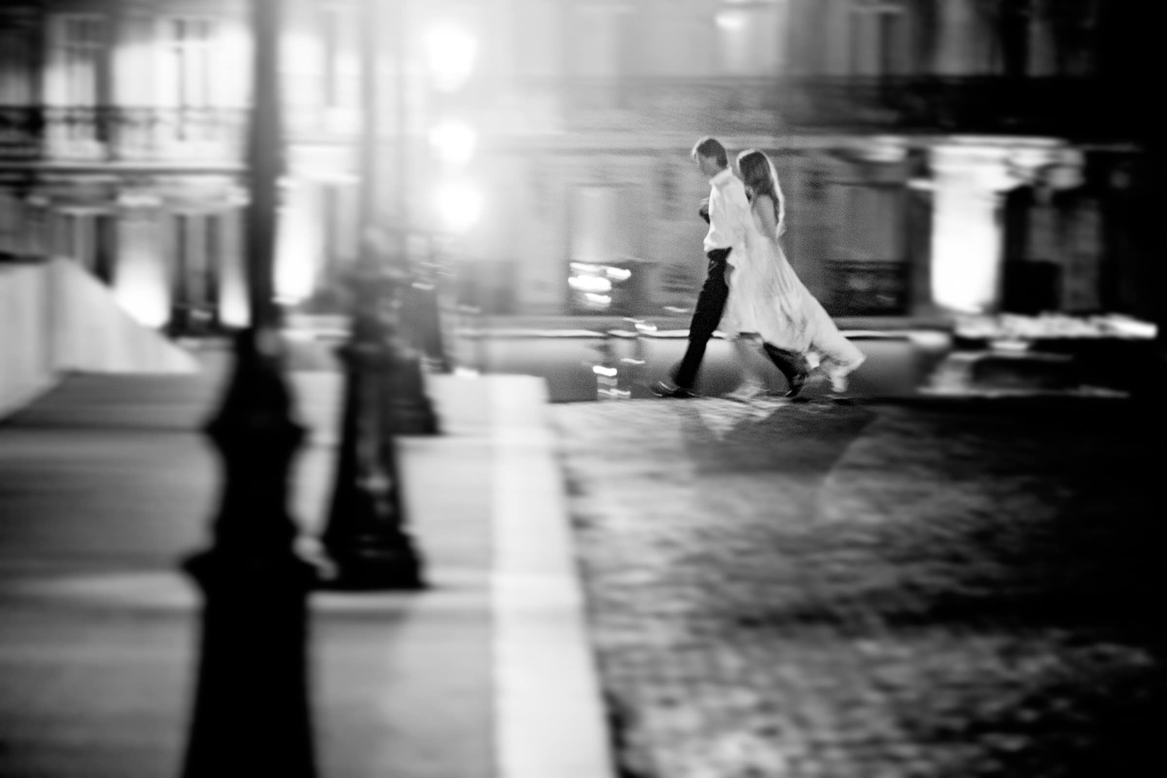Dynamic photo of bride and groom walking along the bridges at night during their Paris engagement date