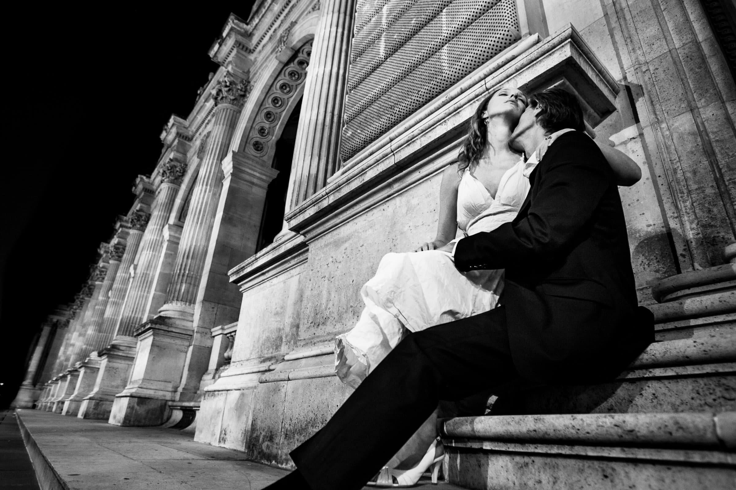 Bride and groom embracing outside the Louvre at night during their Paris engagement date