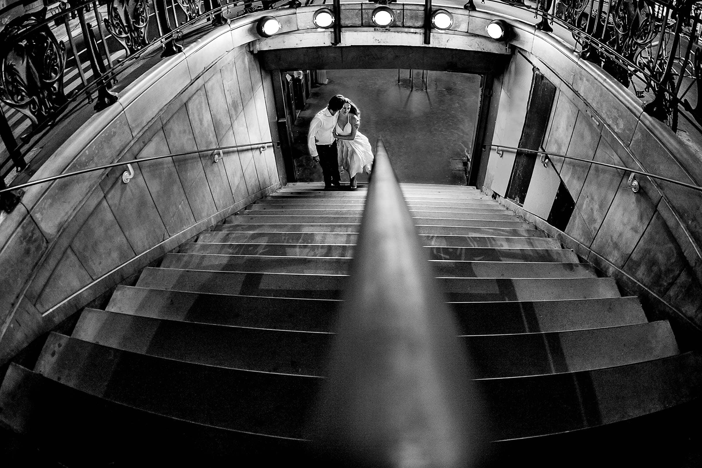 Bride and groom walking up a subway staircase at night during their Paris engagement date