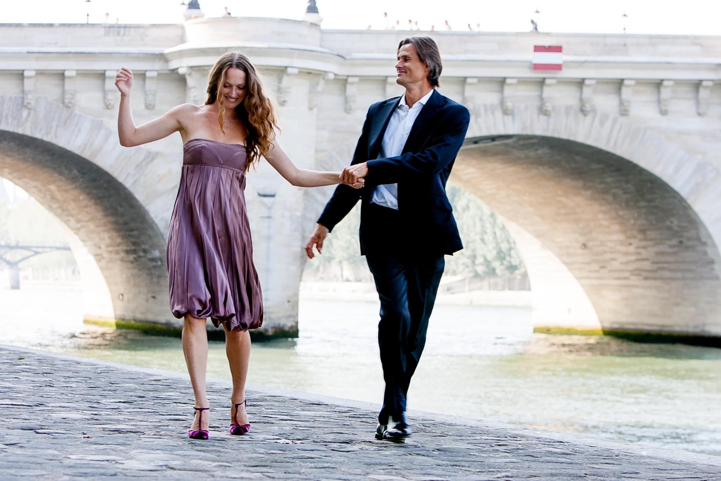 Gorgeous couple walking under bridges near the Seine river during their Paris engagement date