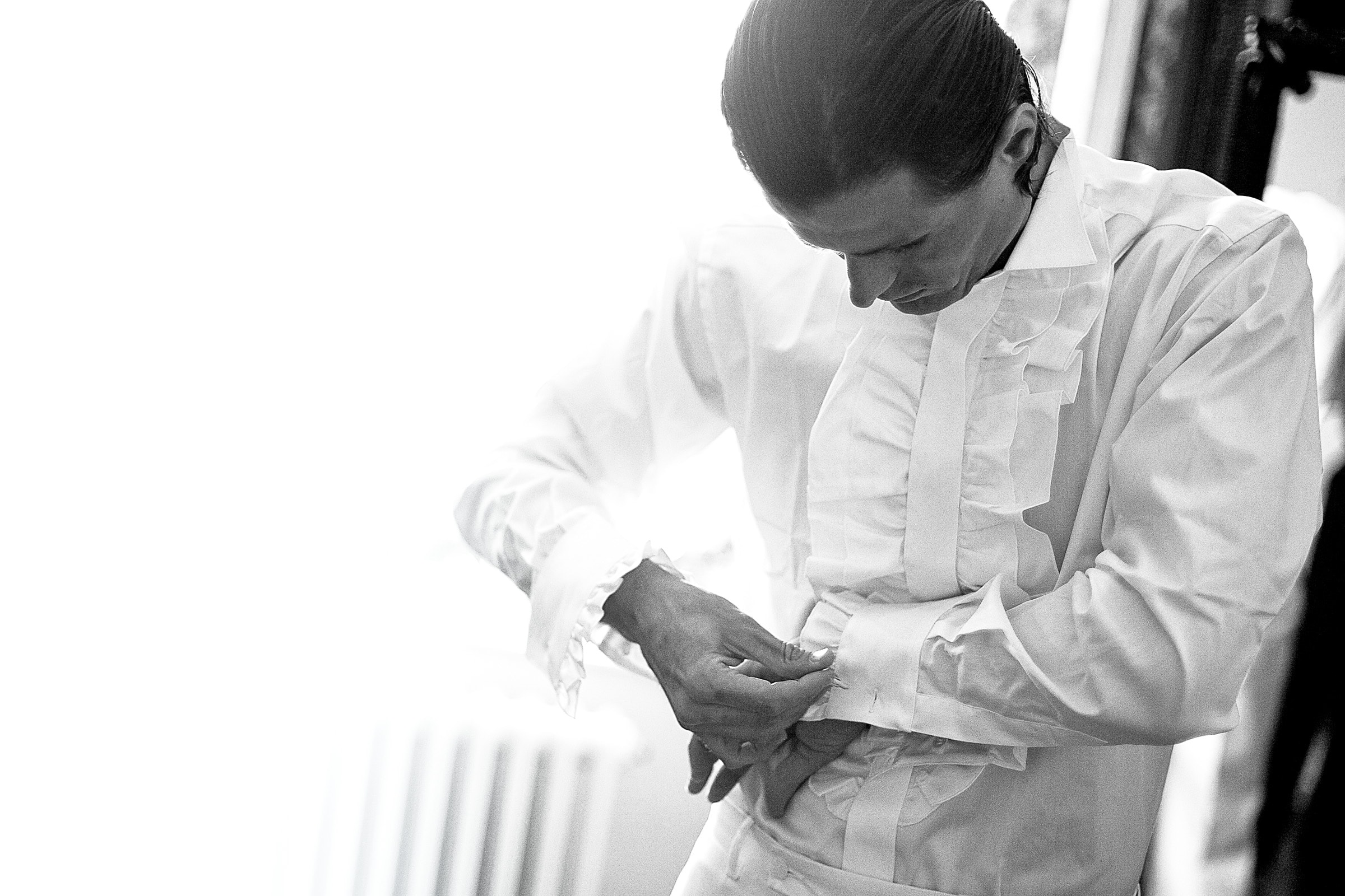 Groom getting ready for his French chateau wedding in South of France while putting on a ruffled wedding shirt