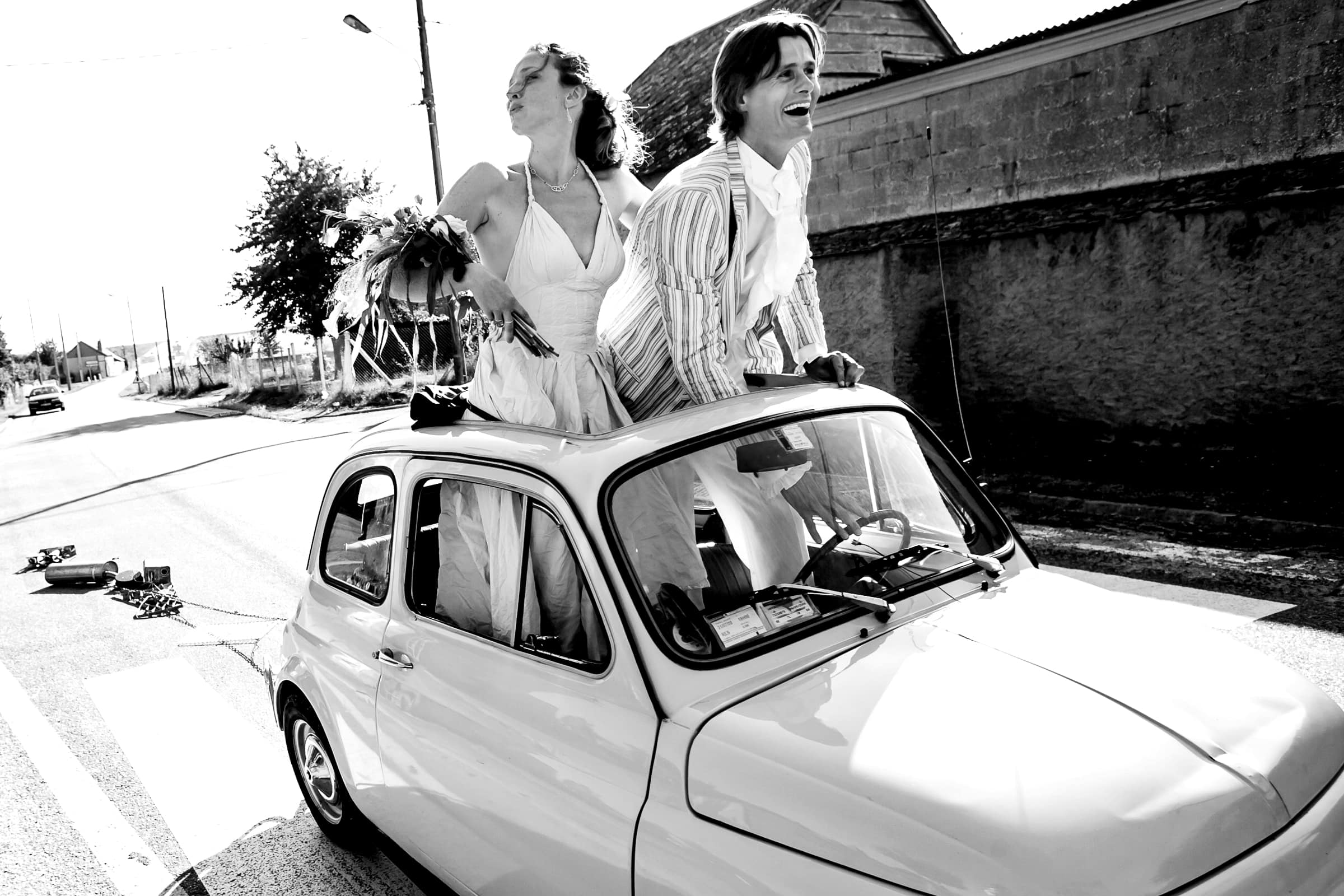 Bride and groom riding in a tiny French car toward their French chateau wedding at Manoir des Prevanches in South of France