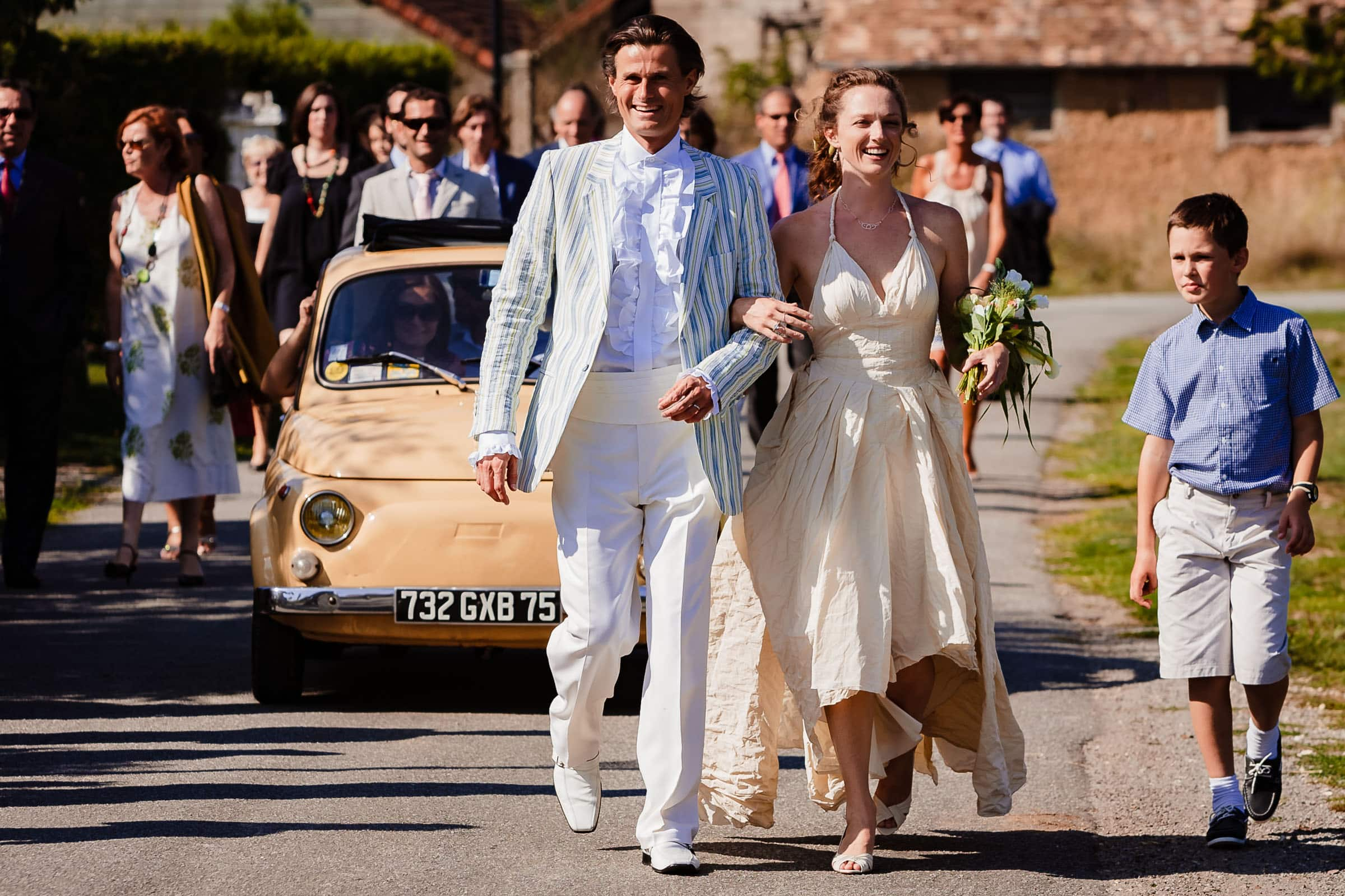 Bride and groom walking to their French chateau wedding sy Manoir des Prevanches in South of France