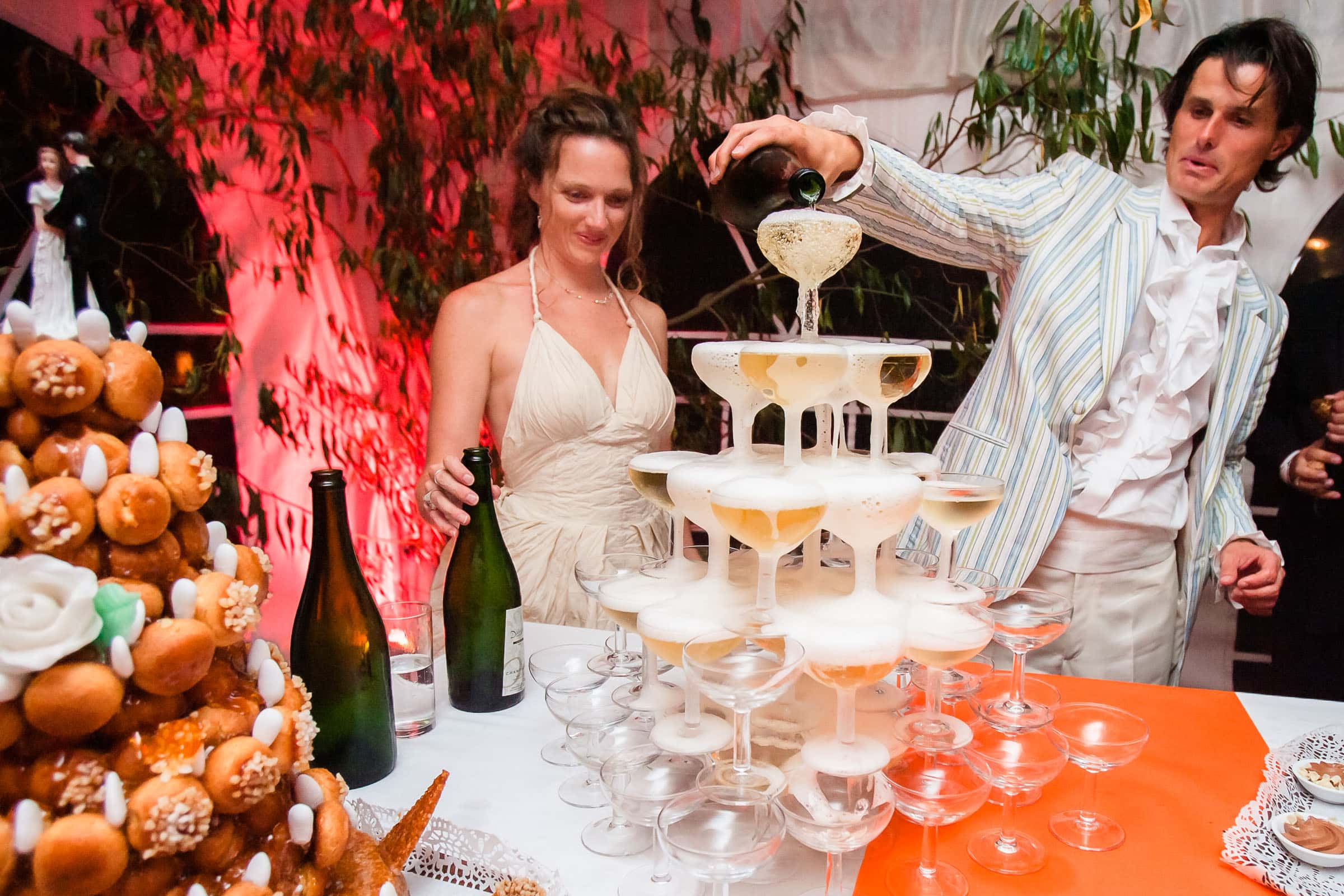 Bride and groom pouring their champagne pyramid during their south of france chateau wedding at Manoir des Prevanches