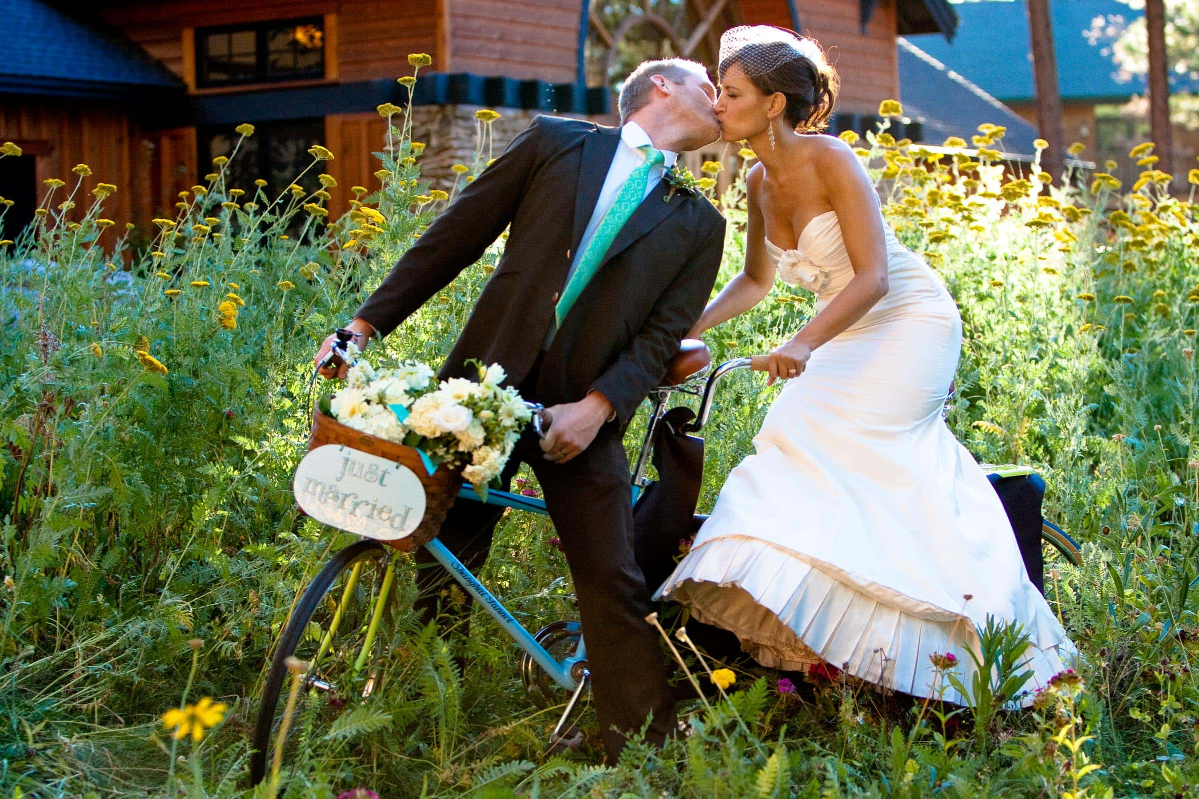 Bride and groom on a tandum bike in a flower field during their Five Pine Lodge wedding in Sisters Oregon near Bend