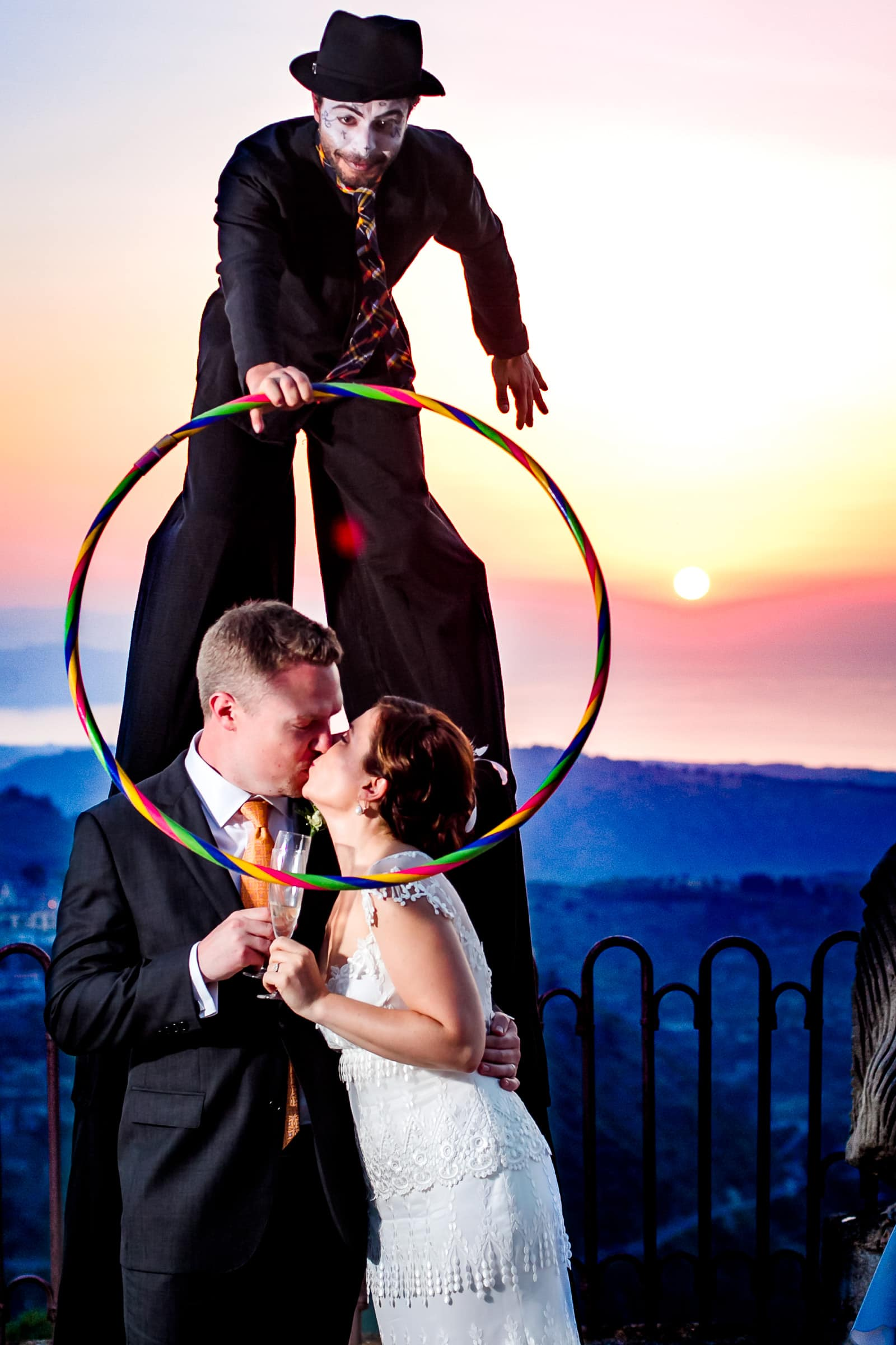 Bride and groom comically greeted by a circus clown on stilts during their Sicily Wedding reception for a sunset potrait