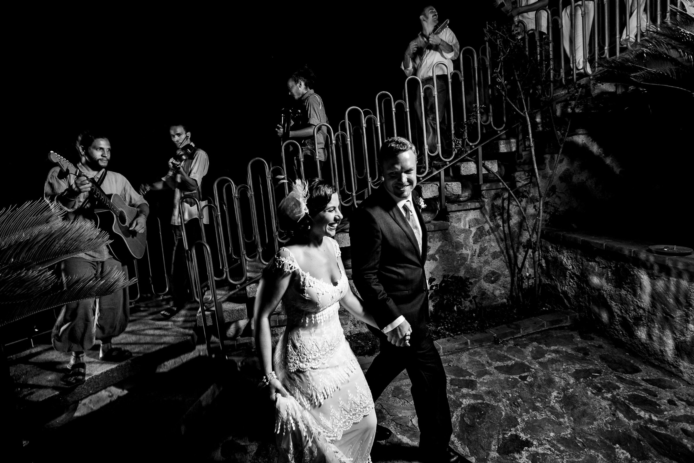 Bride and groom walking into their Sicily wedding reception with musicians playing guitar and singing