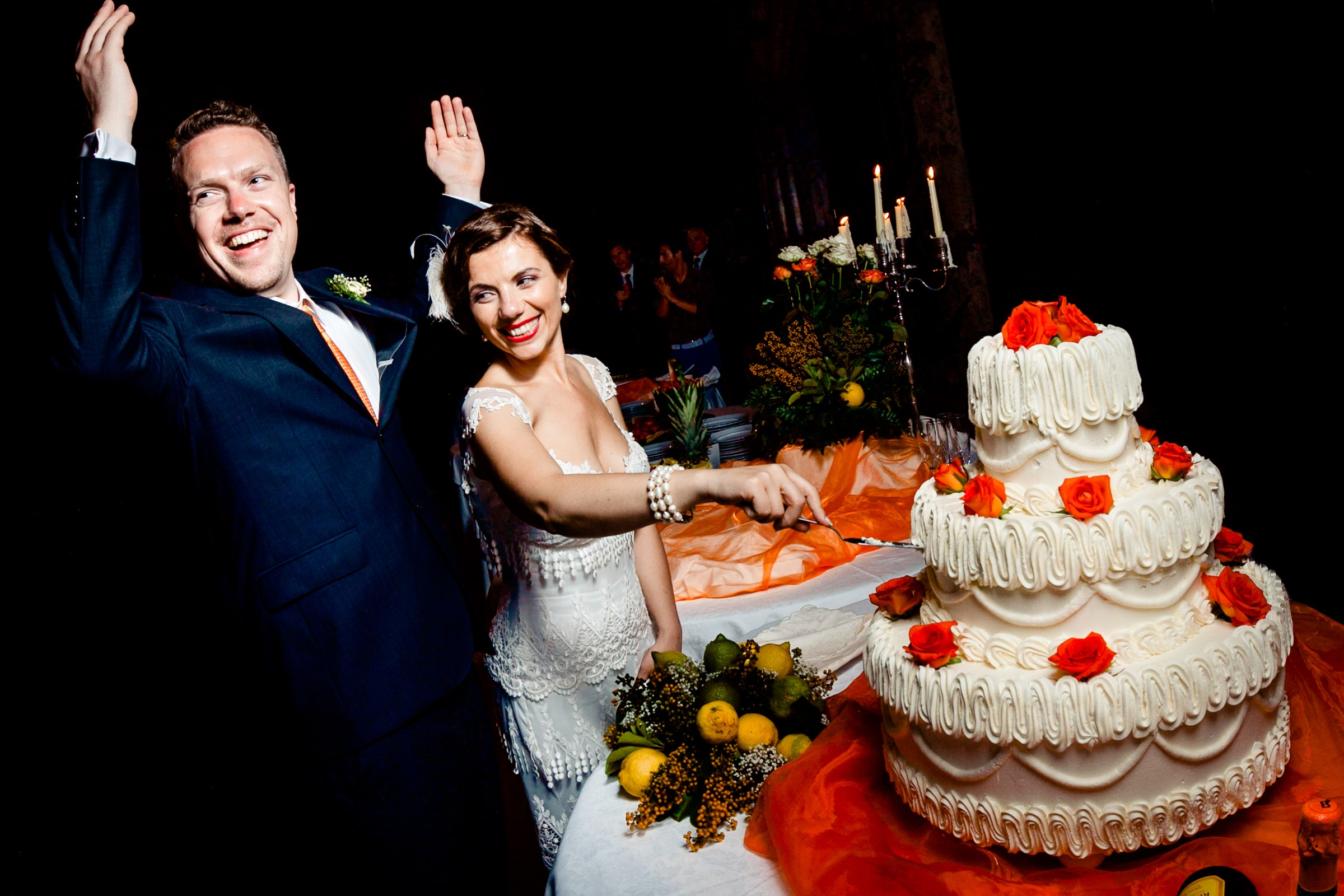 Bride and groom cutting epic Sicily wedding cake during their wedding reception at Parco Museo Jalari