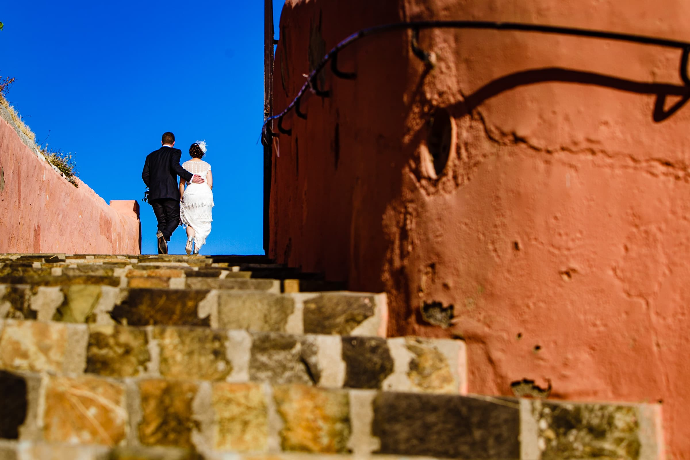 Bride and groom walking up stairs shortly after their Sicily Wedding ceremony in Milazzo, Italy