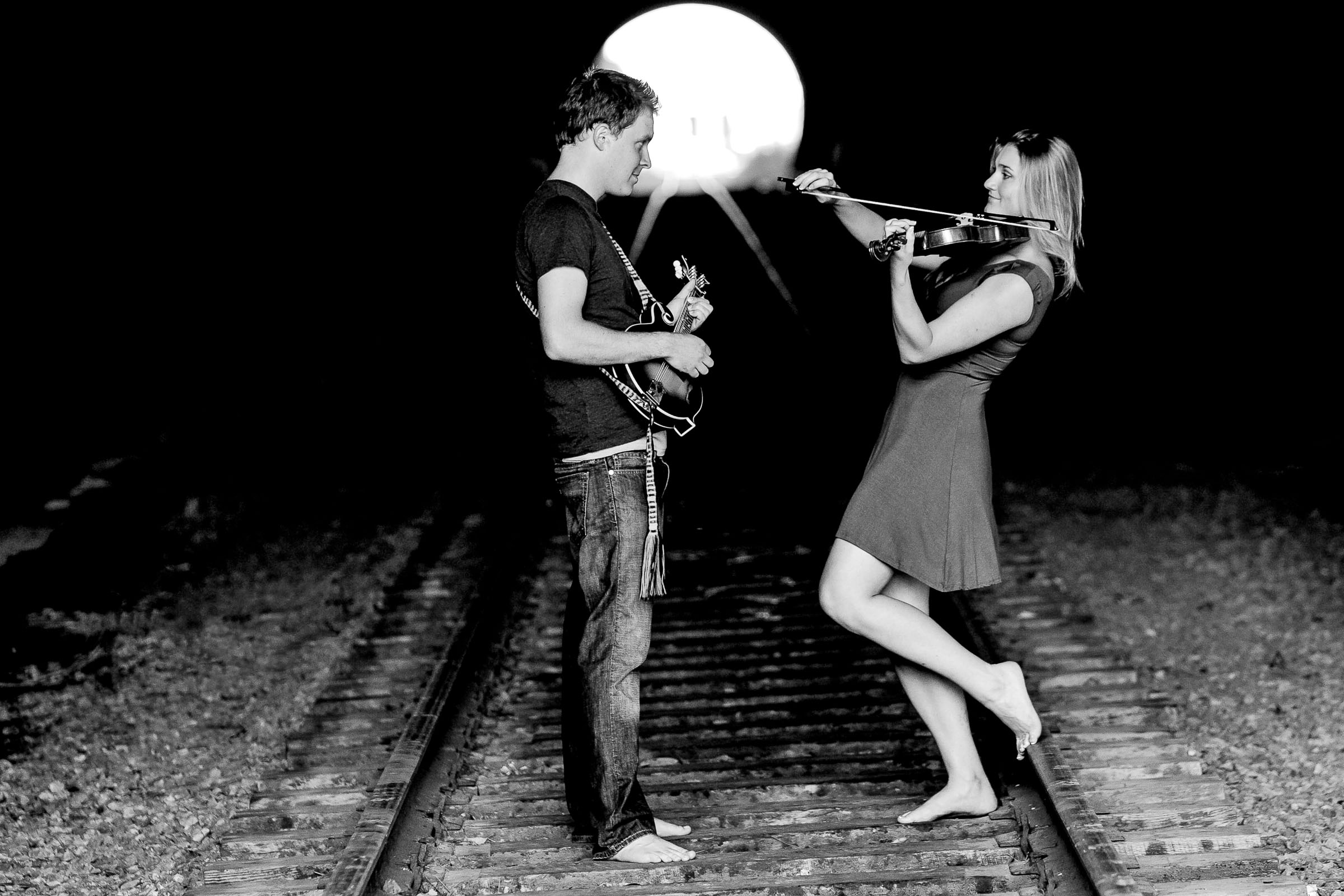 Engagement photo in San Francisco tunnel with a violin and a mandolin. Fun captivating photo.