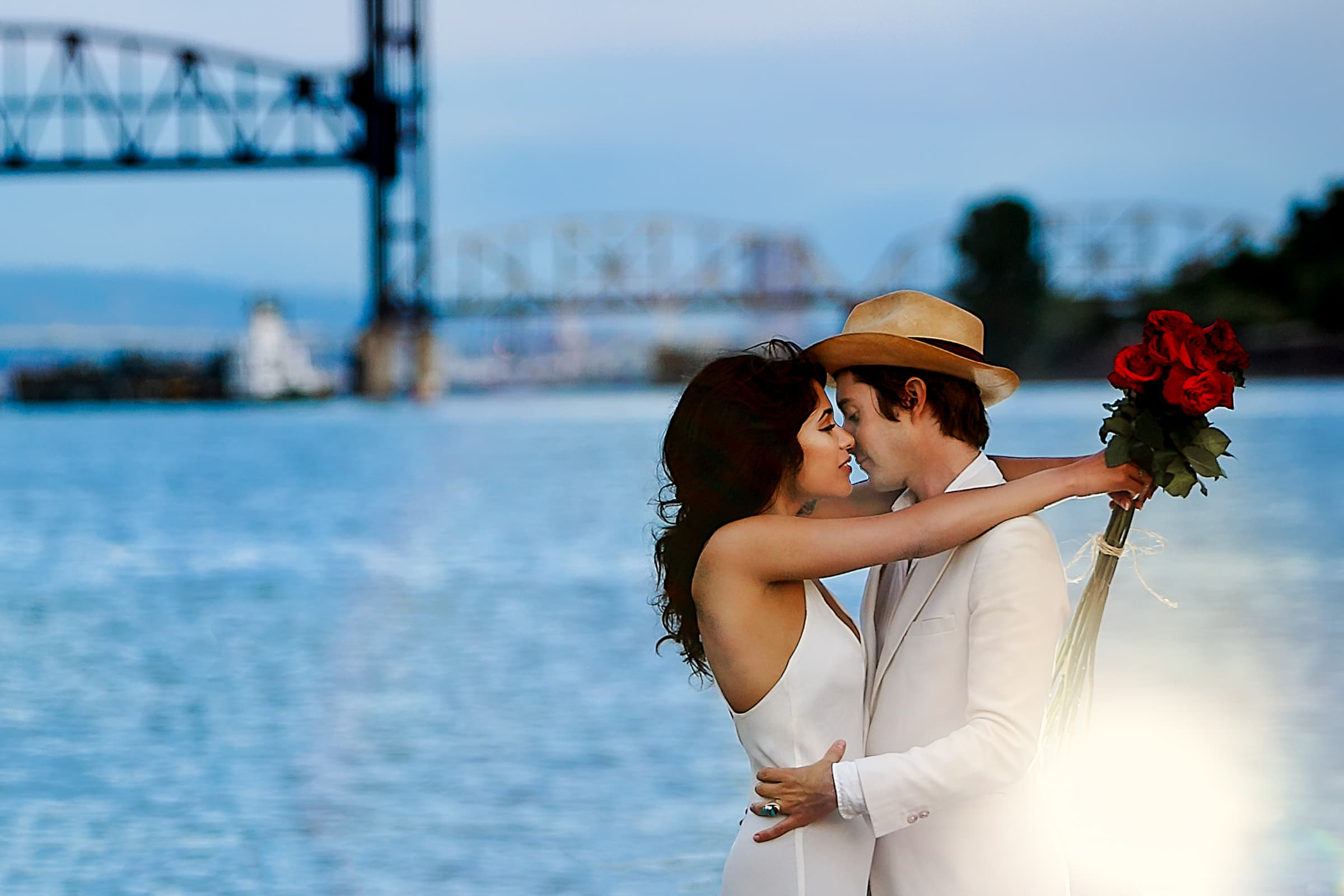 Engagement couple beautifully lit with flowers and authentic embrace in Portland under St Johns Bridge