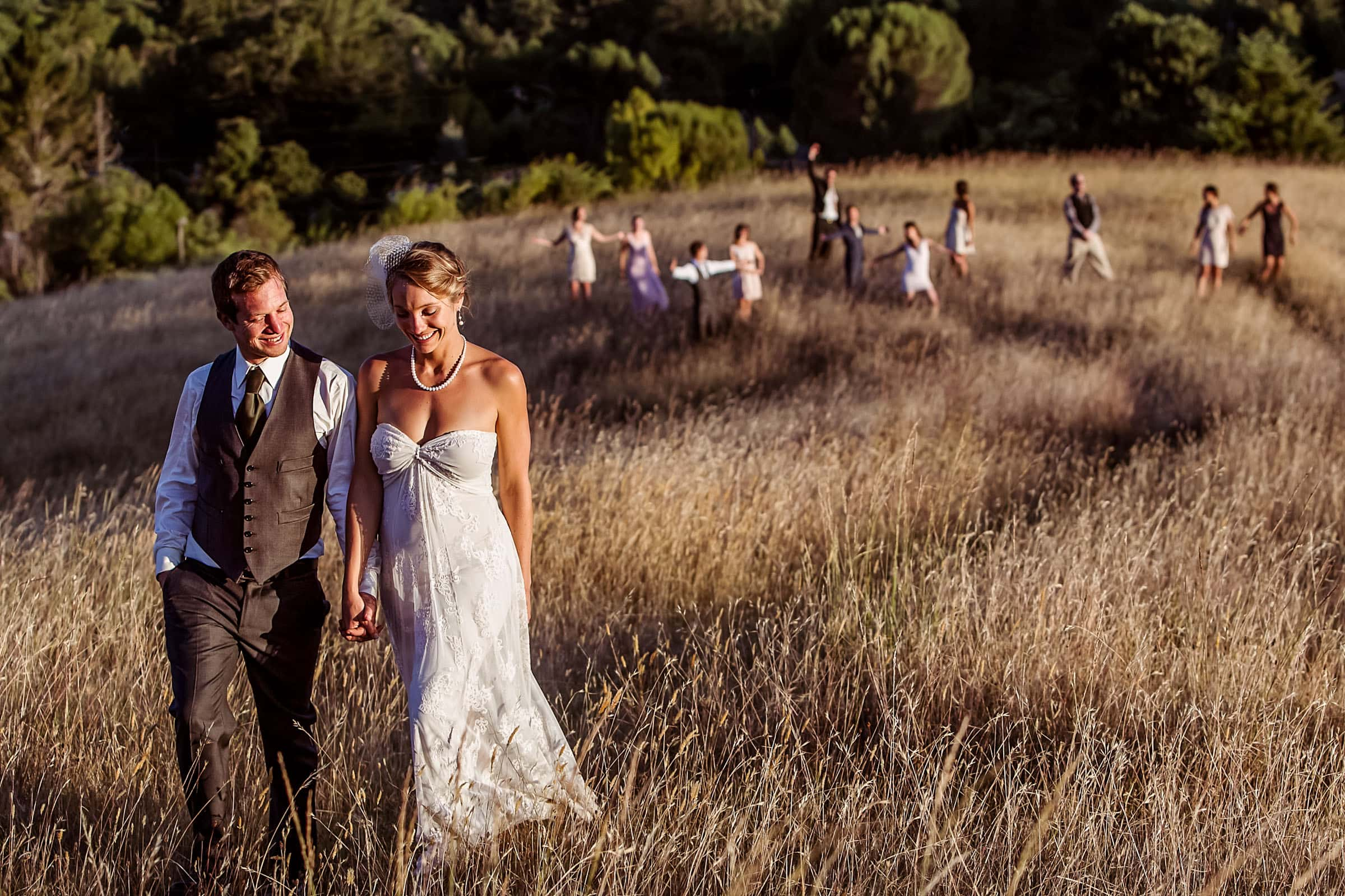 Award winning photo of a bride and groom walking in a field at golden hour with friends celebrating behind them during their Humboldt California wedding at Beginnings Briceland