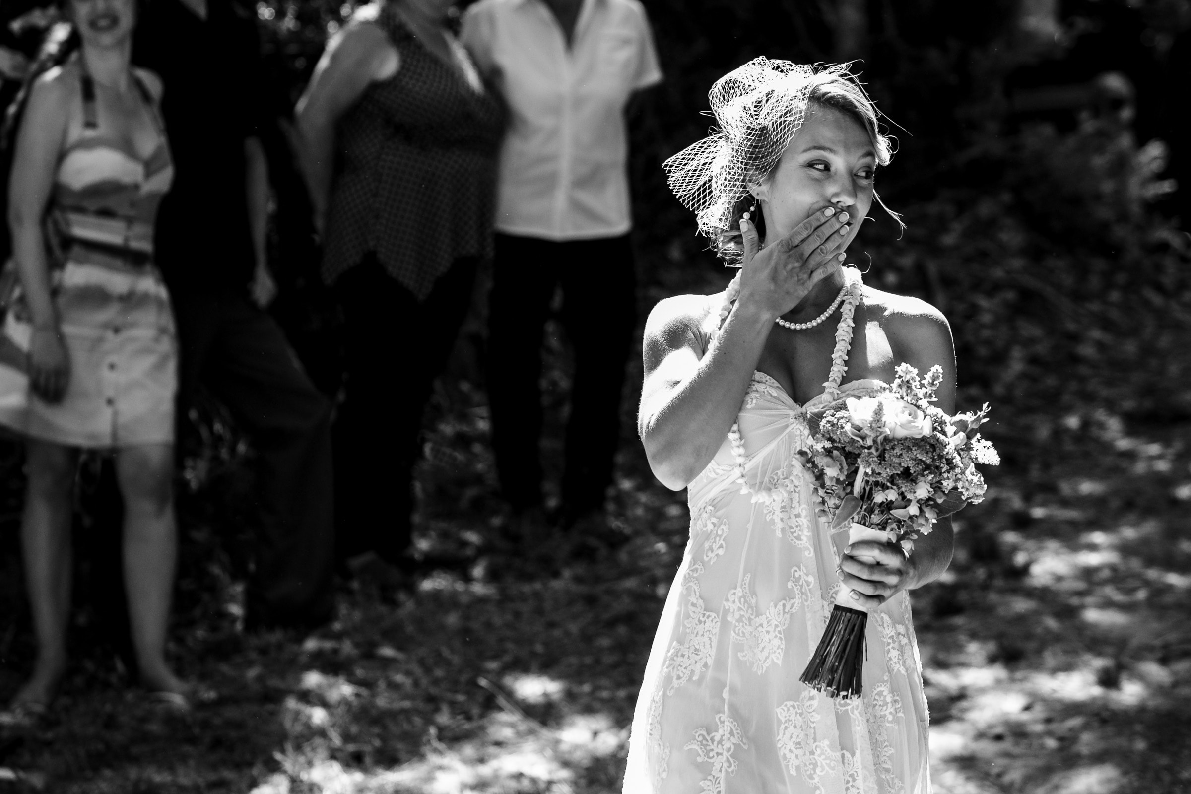 A bride blowing kisses to family and friends during a Humboldt California wedding ceremony at Beginnings Briceland