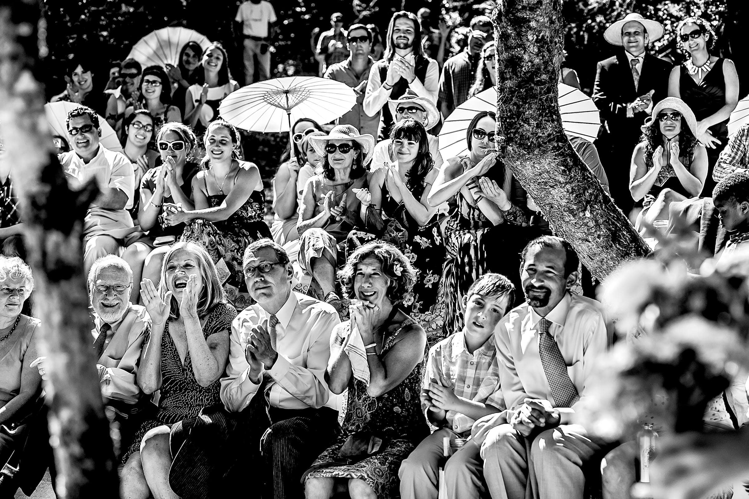 An award winning wedding photo of family and friends reacting to the bride and groom during their Humboldt California wedding ceremony at Beginnings Briceland