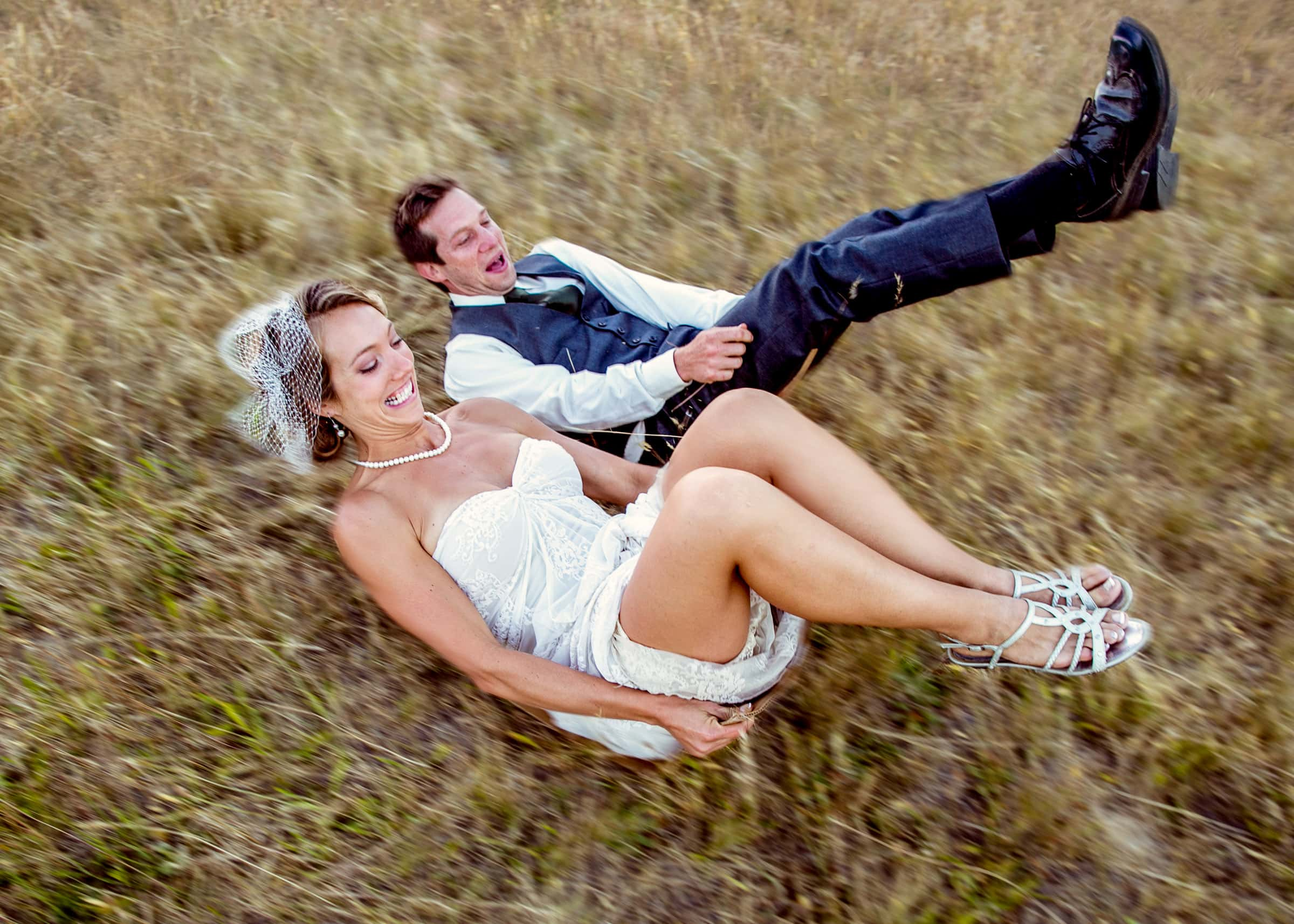 a happy bride and groom sliding on cardboard down a wheat field at sunset before heading into their Humboldt California wedding reception at Beginnings Briceland