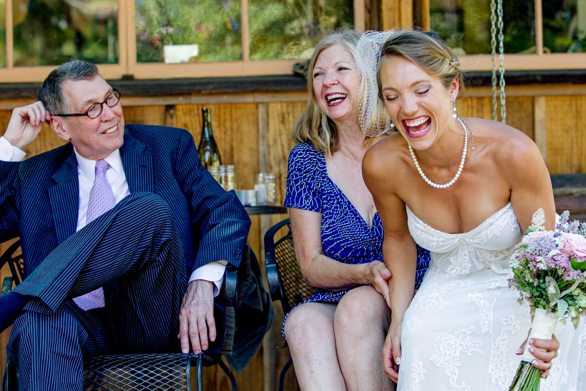 A happy bride laughing with parents moments before her Humboldt California wedding at Beginnings Briceland