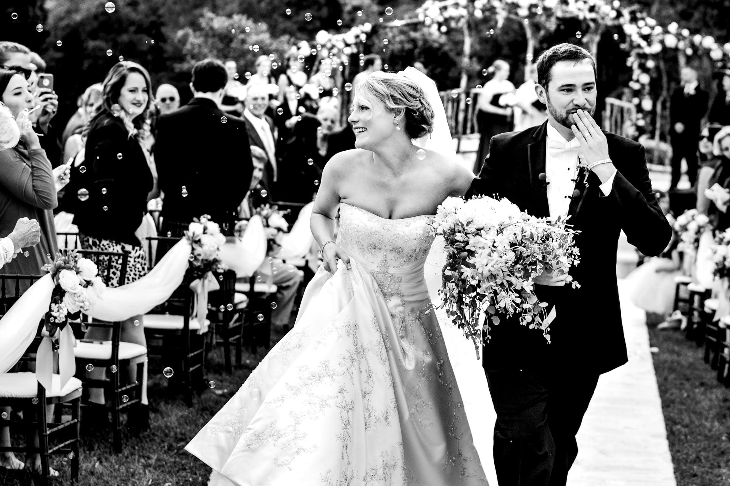 Gorgeous capture of a bride and groom blowing kisses to family and friends as they exit their Trapp Family Lodge wedding in Stowe, Vermont.