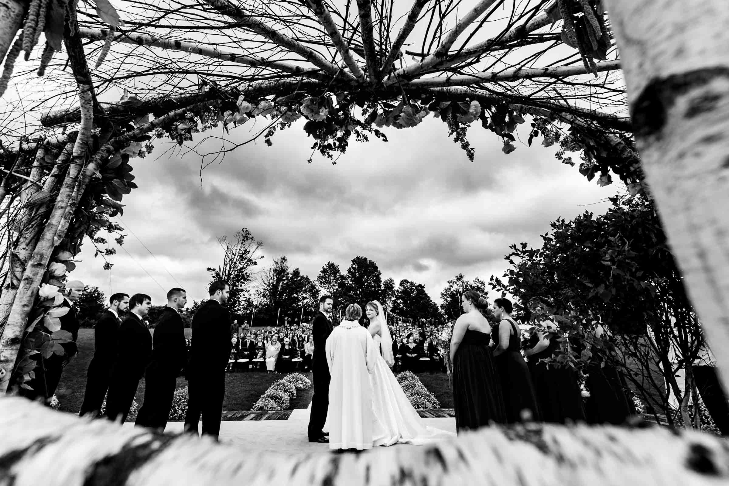 Wide angle view of the bride and groom and their bridal party during their Trapp Family Lodge wedding ceremony in Stowe, Vermont.