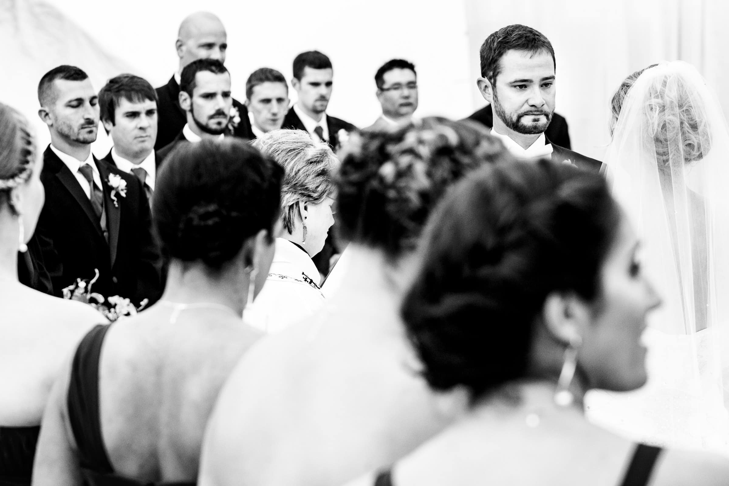 Emotional photo of a groom layered inside the bridal party during a Trapp Family Lodge wedding ceremony in Stowe, Vermont.