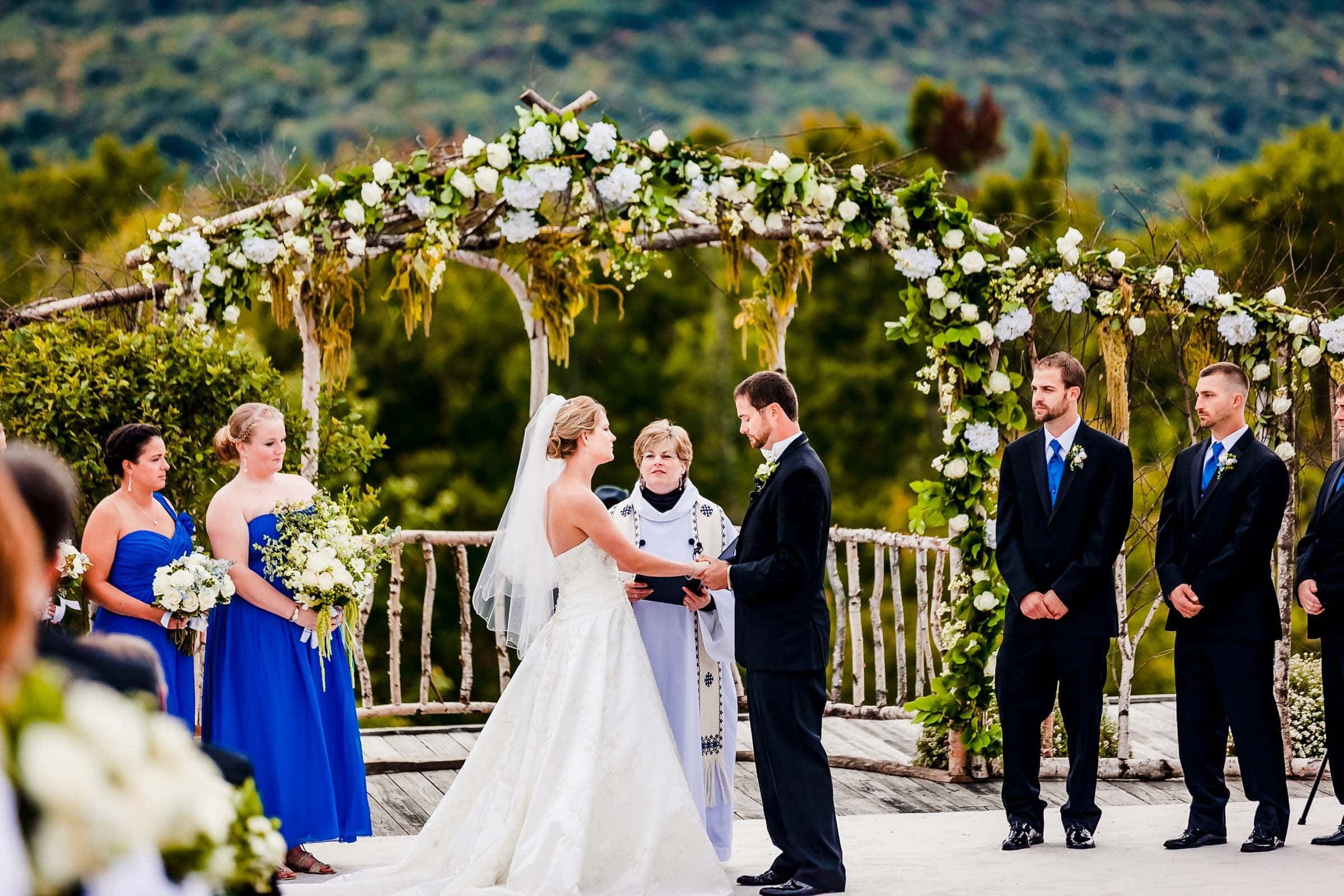 Bride and groom exchanging vows with a vast background view during their Trapp Family Lodge wedding ceremony in Stowe, Vermont.