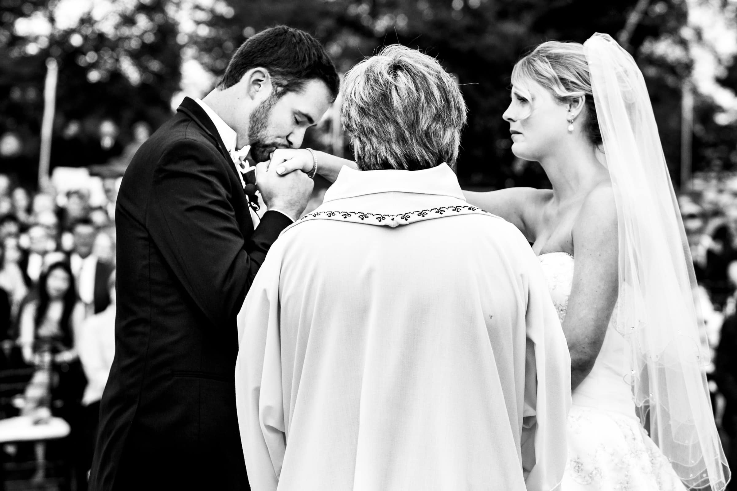 Emotional photo of a groom kissing his brides hand during their Trapp Family Lodge wedding ceremony in Stowe, Vermont.