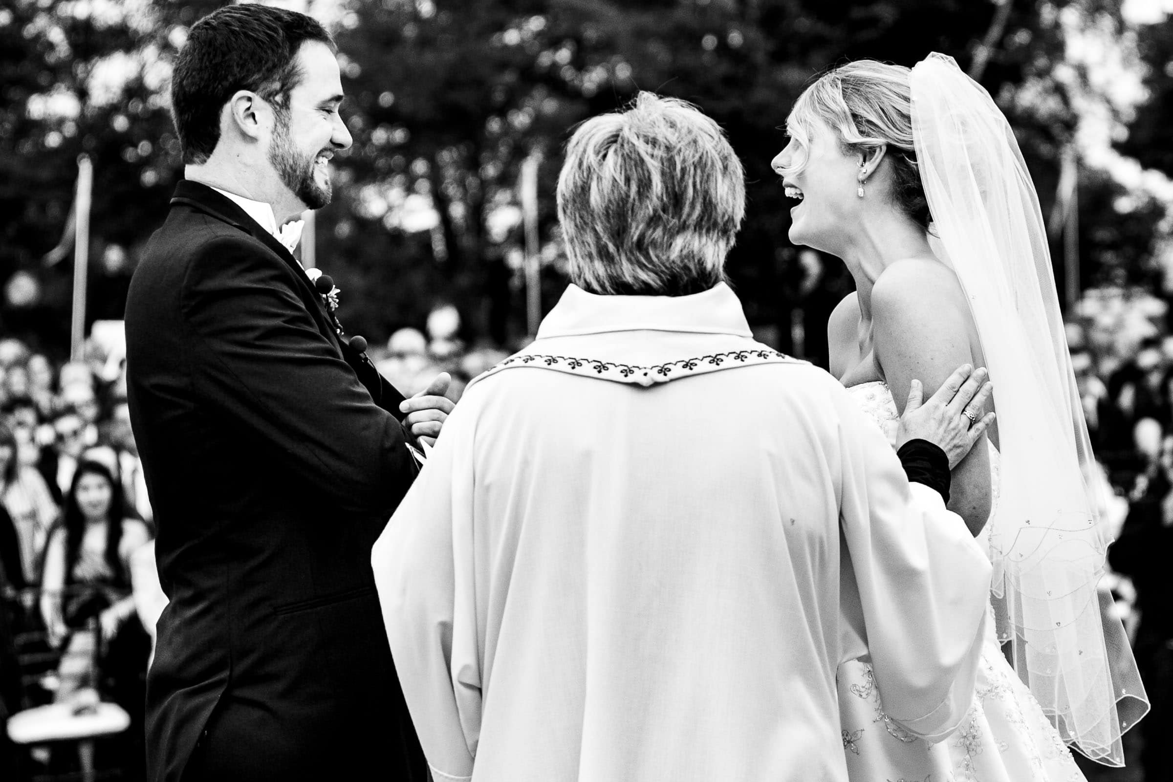 Bride and groom laughing during their Trapp Family Lodge wedding ceremony in Stowe, Vermont.