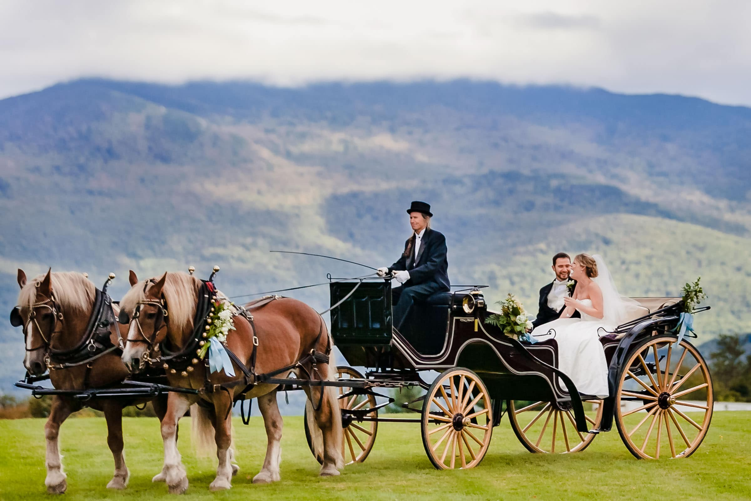 Bride and groom in hysterical laughter while riding in a horse and buggy exiting their Trapp Family Lodge wedding ceremony in Stowe, Vermont.
