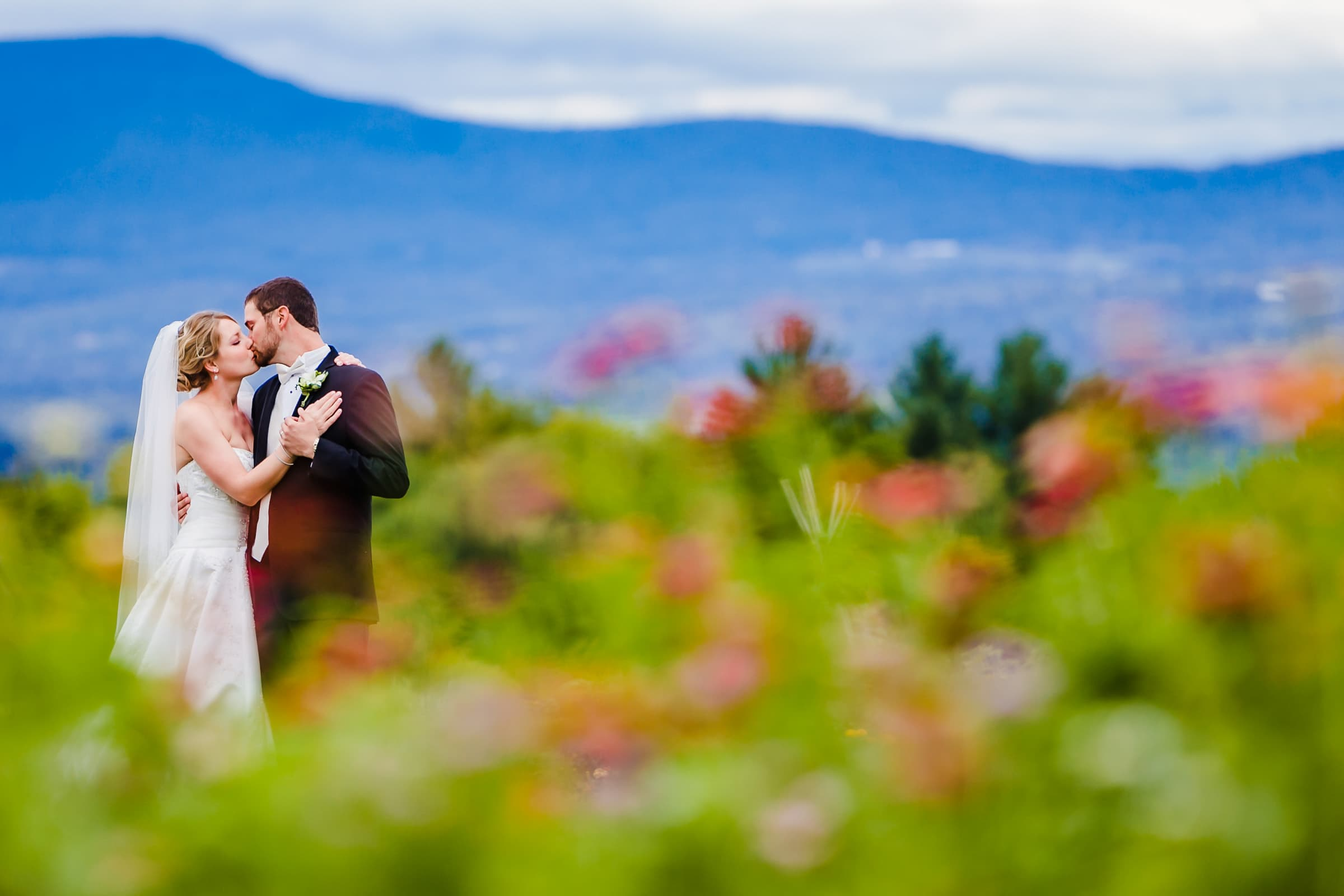 Bride and groom embracing in a flower field following their Trapp Family Lodge wedding ceremony in Stowe, Vermont.