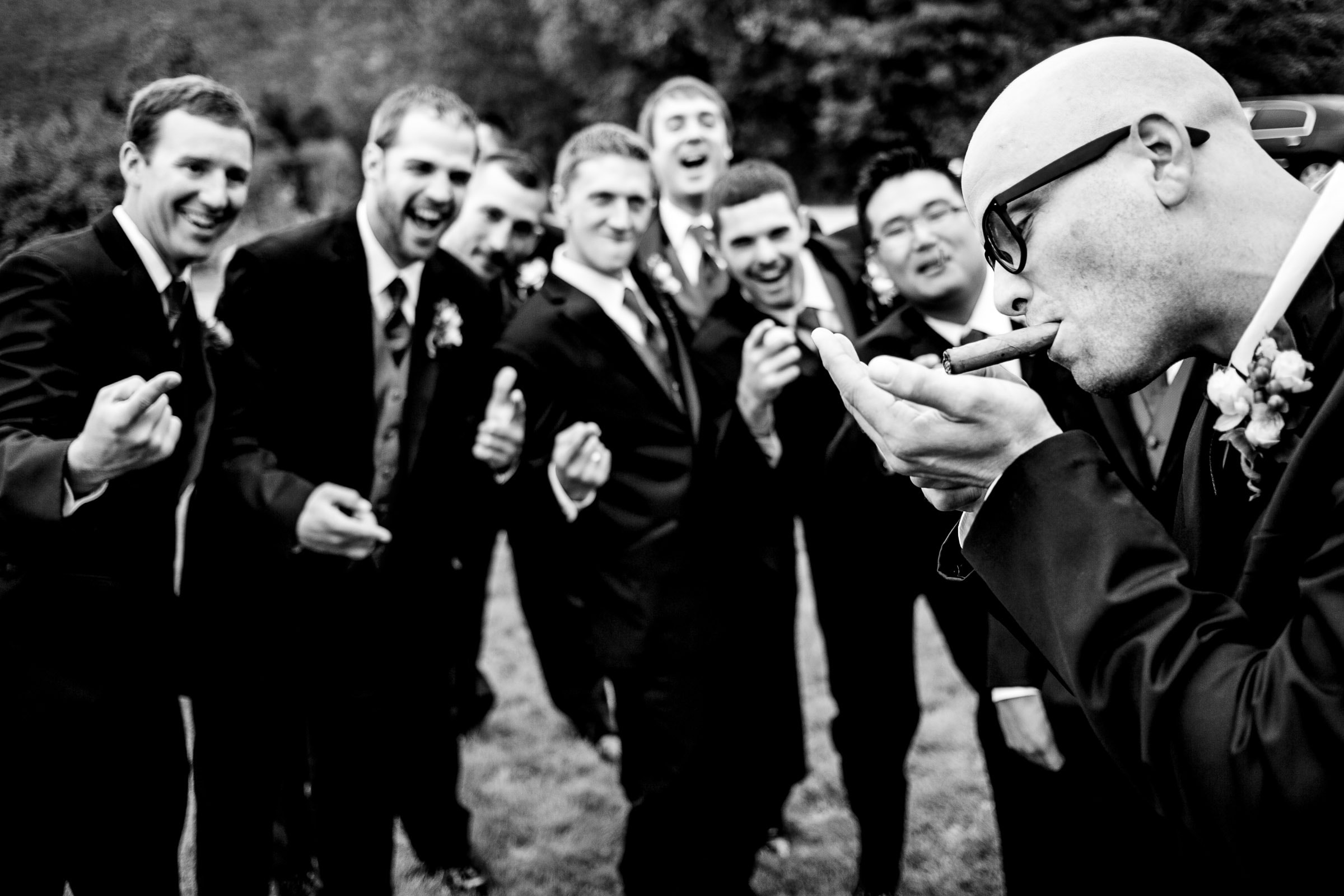 Groomsmen smoking cigars with friends at a Trapp Family Lodge wedding ceremony in Stowe, Vermont.