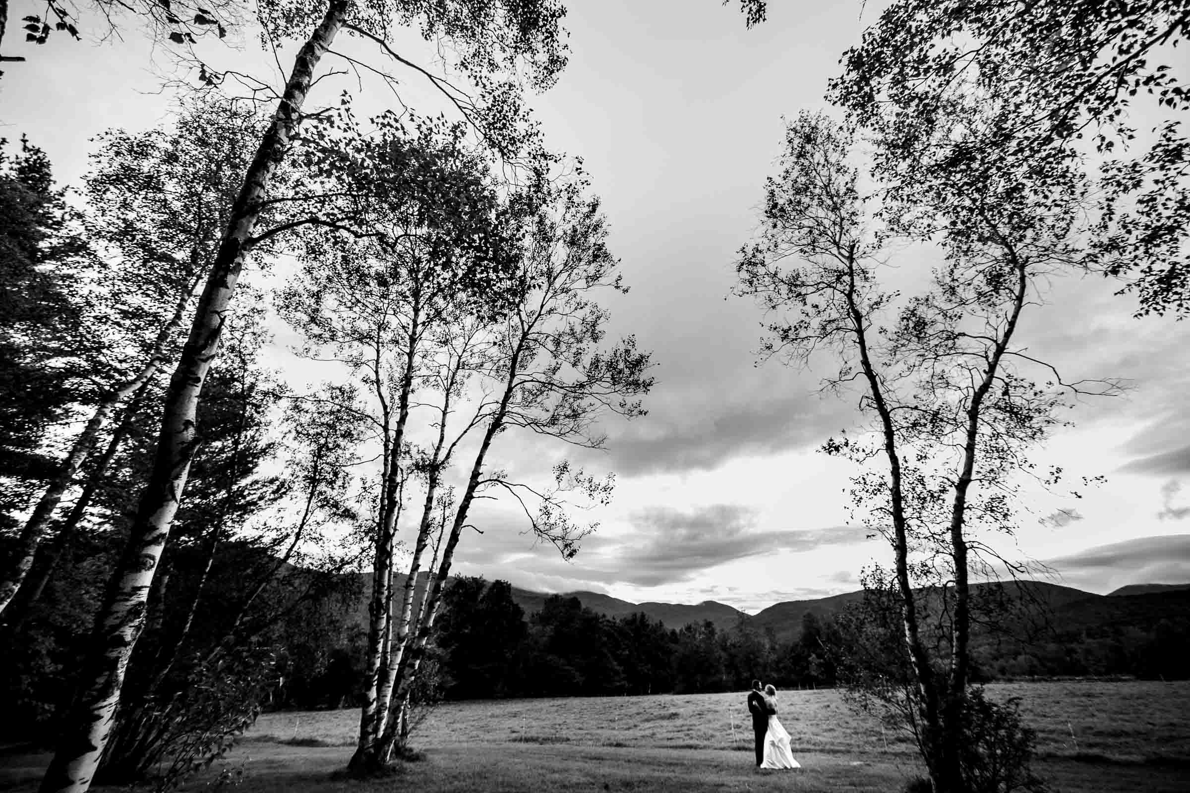 Bride and groom embracing in a big field during a Trapp Family Lodge wedding in Stowe, Vermont.