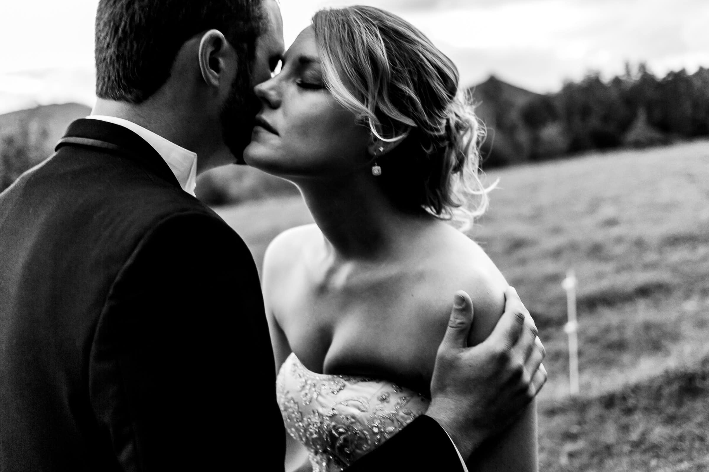A close up and intimate Bride and groom in a field during a Trapp Family Lodge wedding in Stowe, Vermont.