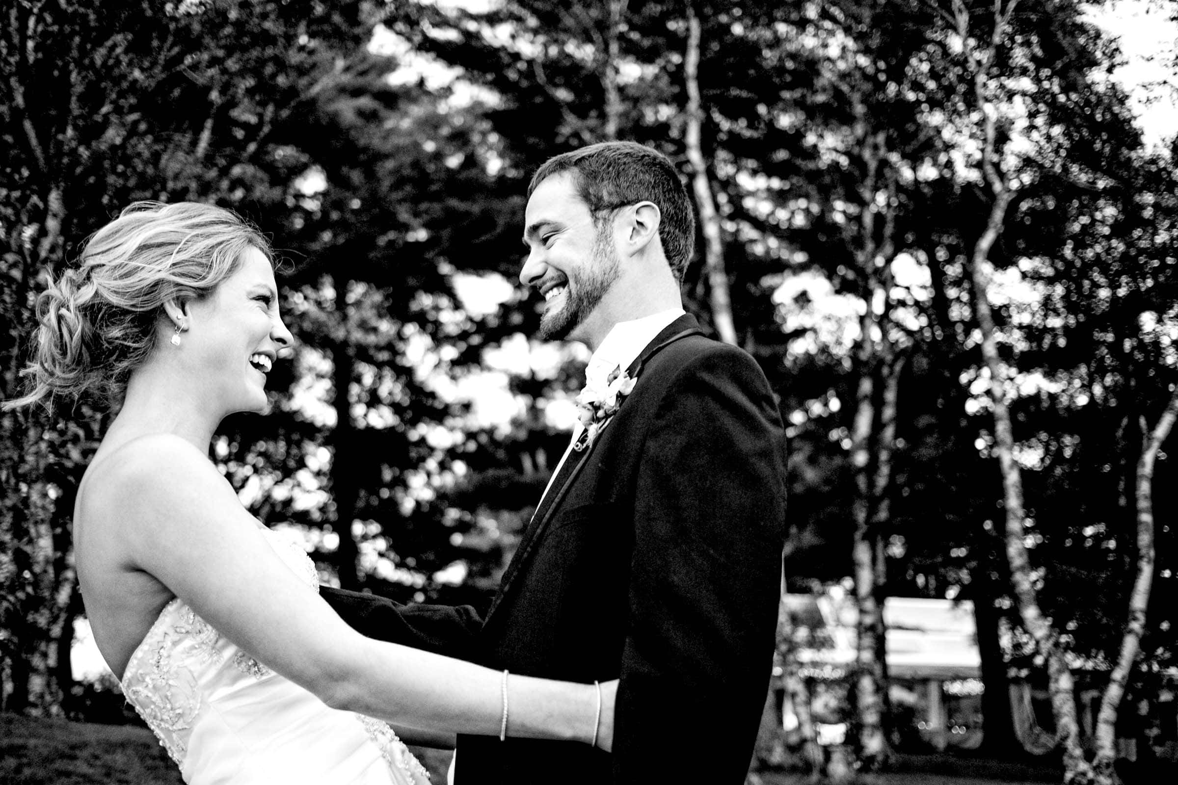 A bride and groom laughing and hugging together during a Trapp Family Lodge wedding in Stowe, Vermont.