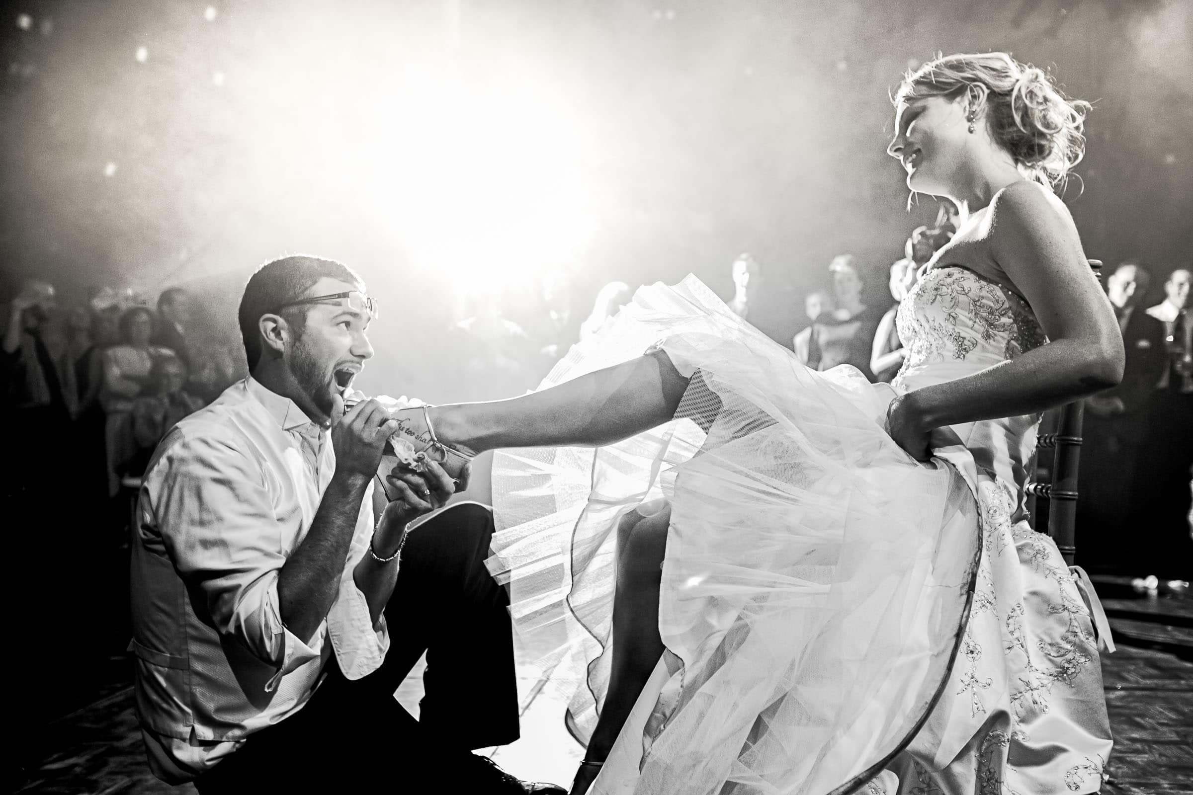 Groom taking the garter off his bride during their Trapp Family Lodge wedding reception in Stowe, Vermont.