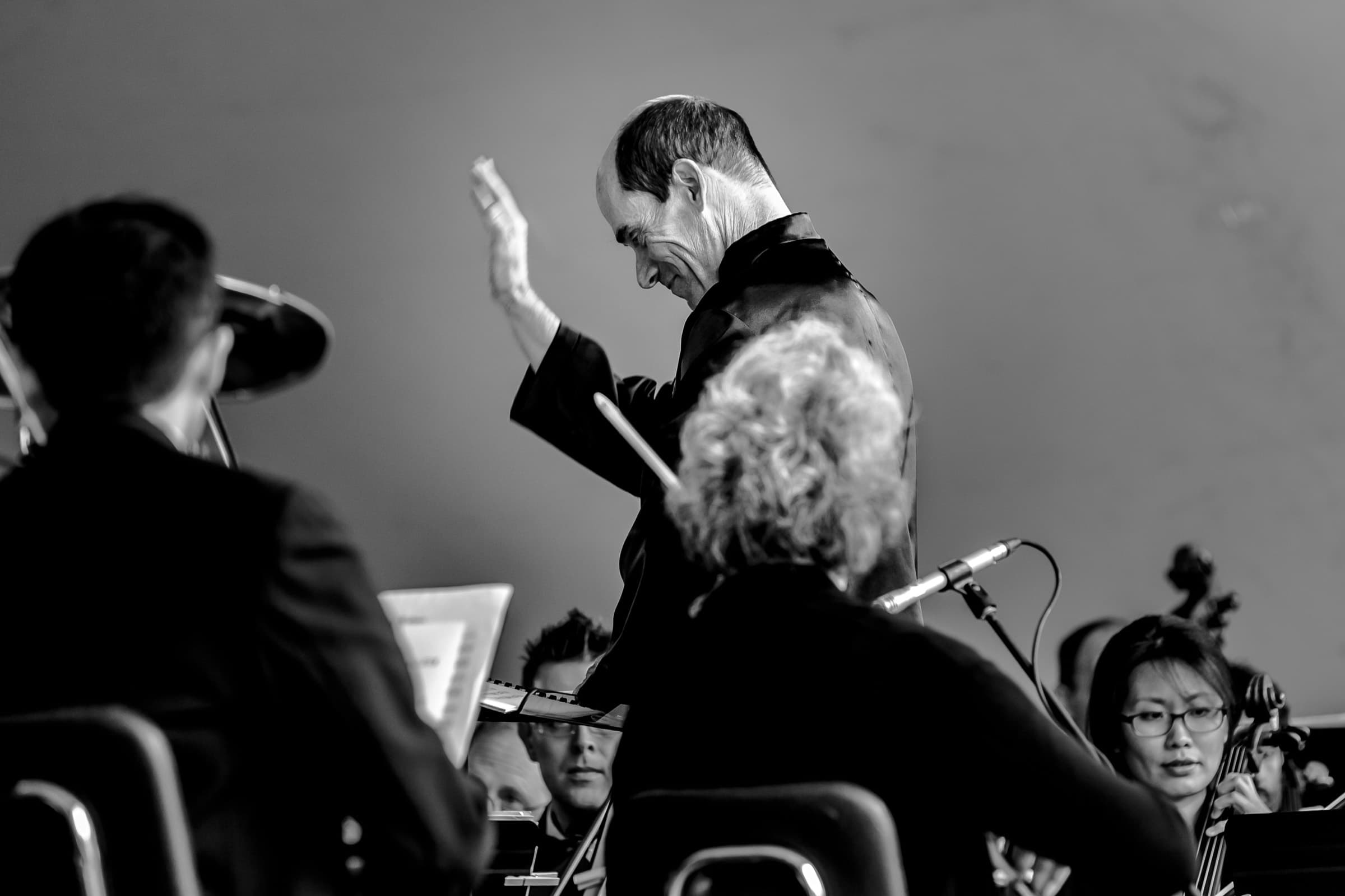 A photo of the Vermont Philharmonic Orchestra conductor performing as Missy walks into her Trapp Family Lodge wedding ceremony in Stowe, Vermont.
