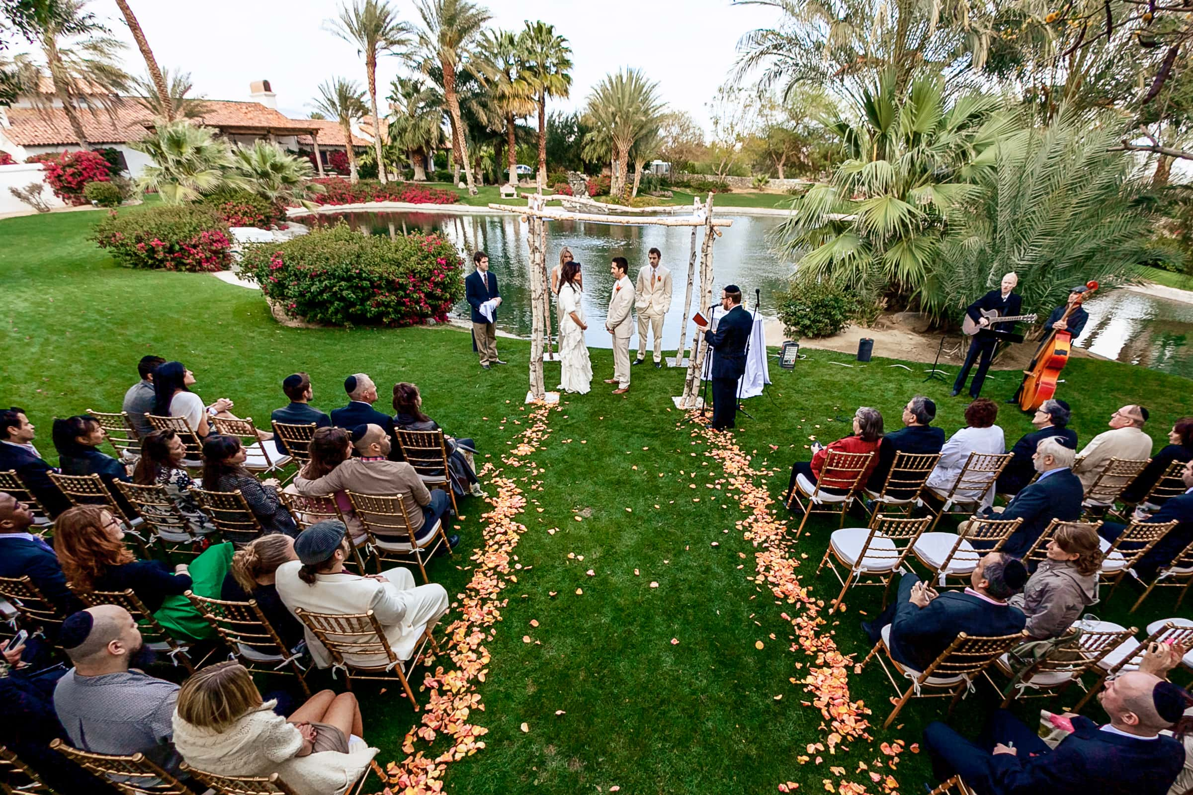 Wide angle photo of Jay Karas and Monica Osborn exchanging vows at their Palm Springs Wedding in California at The Bougainvillea Estate