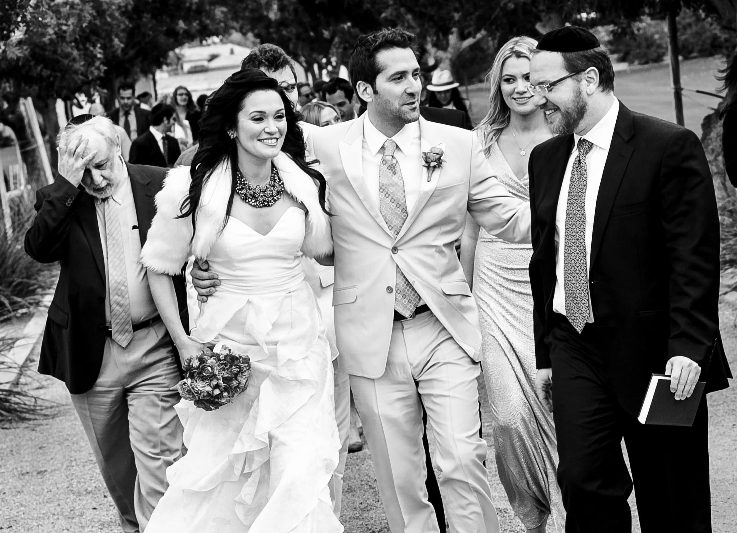Friends and family walking with Jay Karas and Monica Osborn during their Palm Springs Wedding in California at The Bougainvillea Estate