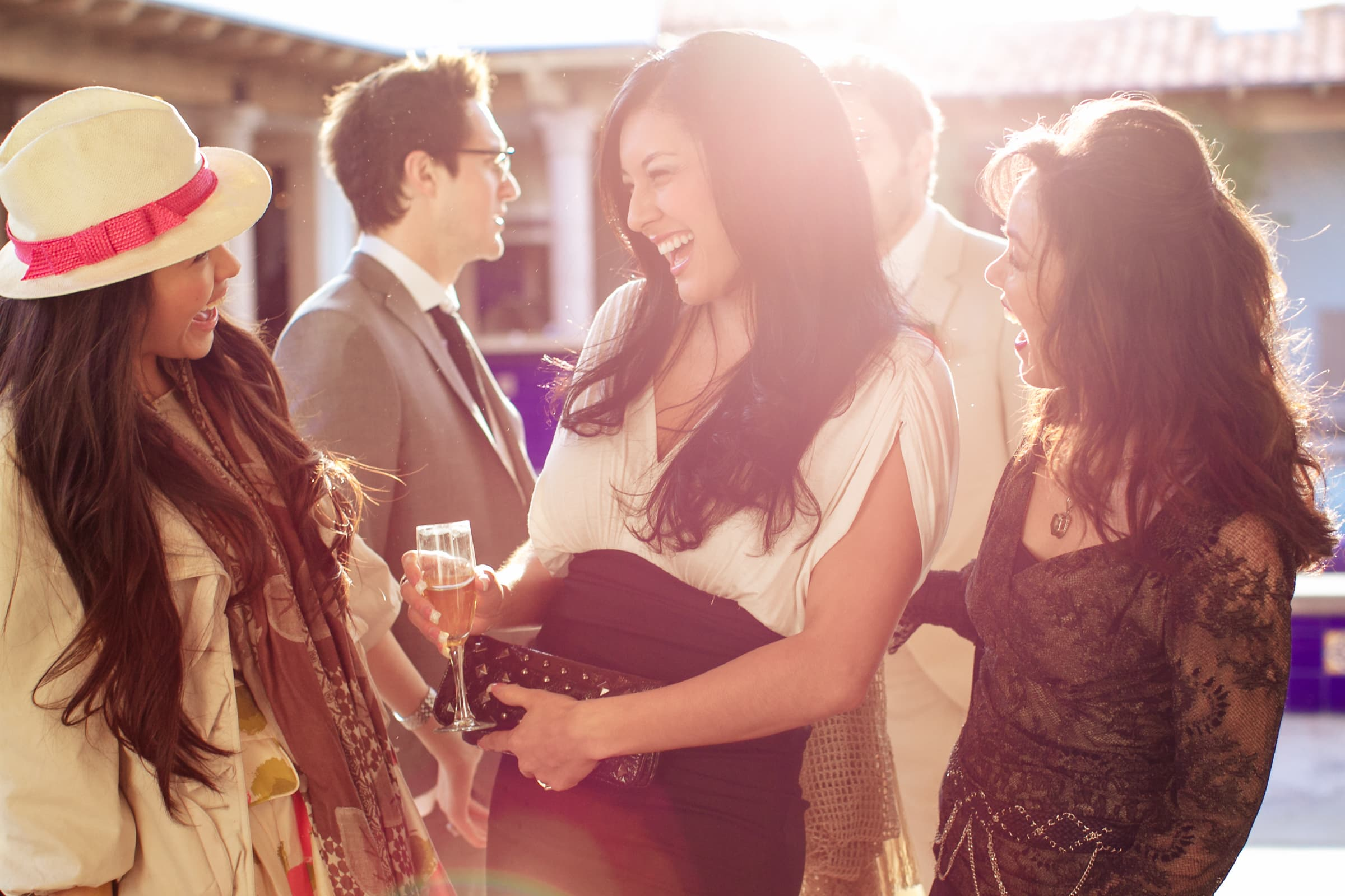Happy friends and family with sun flare with Jay Karas and Monica Osborn during their Palm Springs Wedding reception in California at The Bougainvillea Estate