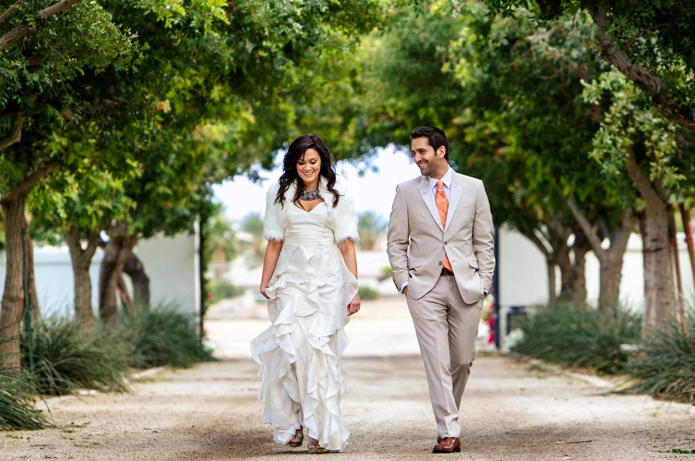 Jay Karas and Monica Osborn walking together at their Palm Springs Wedding in California at The Bougainvillea Estate
