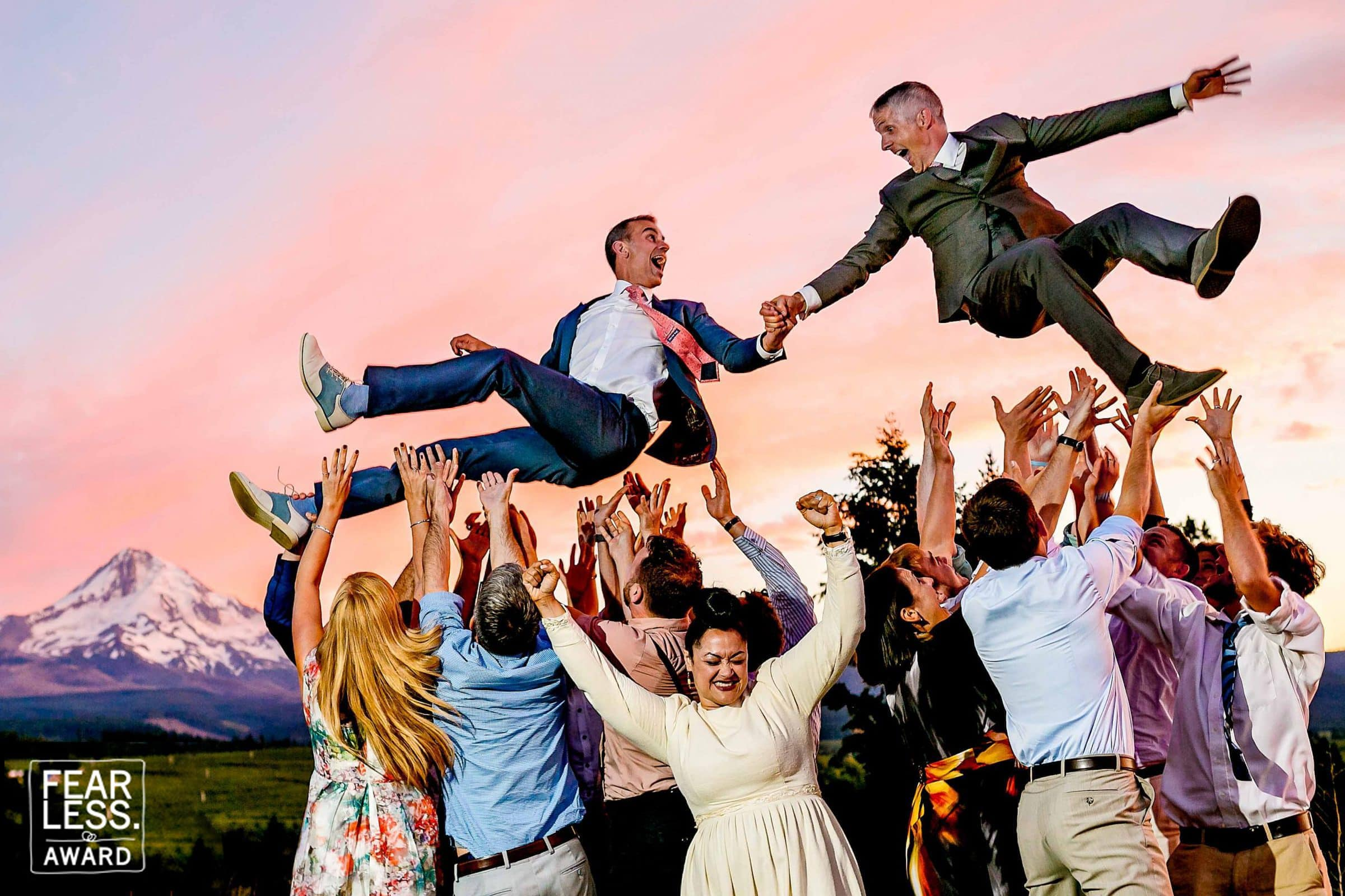 Fearless Photographers award winning photo of two grooms flying in the air holding hands above guests with a mountain view during their Mt Hood Organic Farms Wedding just outside Hood River, Oregon