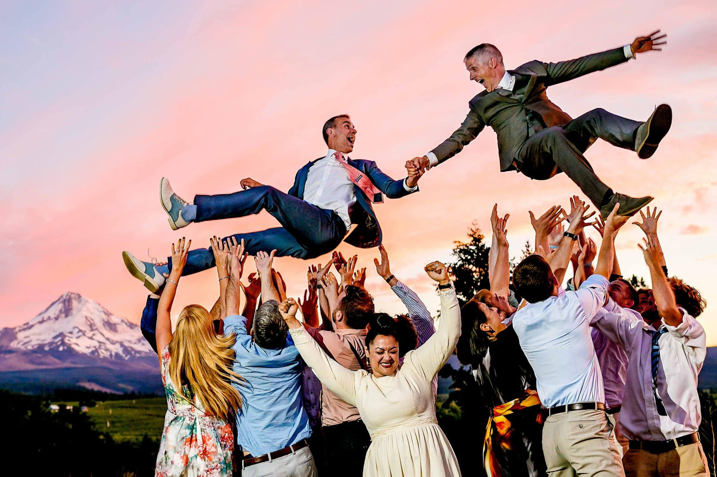 Two grooms flying in the air holding hands above guests with view of Mt Hood at Mt Hood Organic Farms