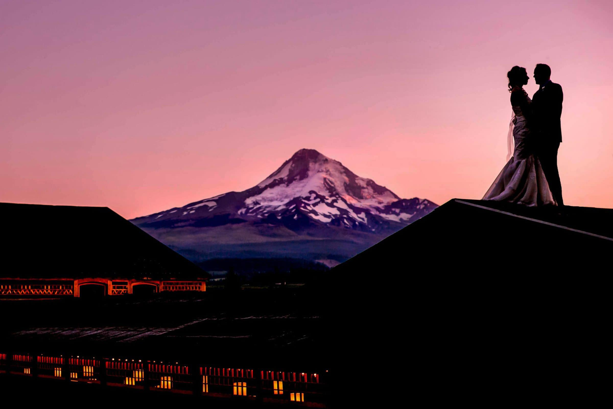 Gorgeous capture of Bride and Groom ontop of Mt Hood Organic Farms rooftop with Mt Hood at sunset