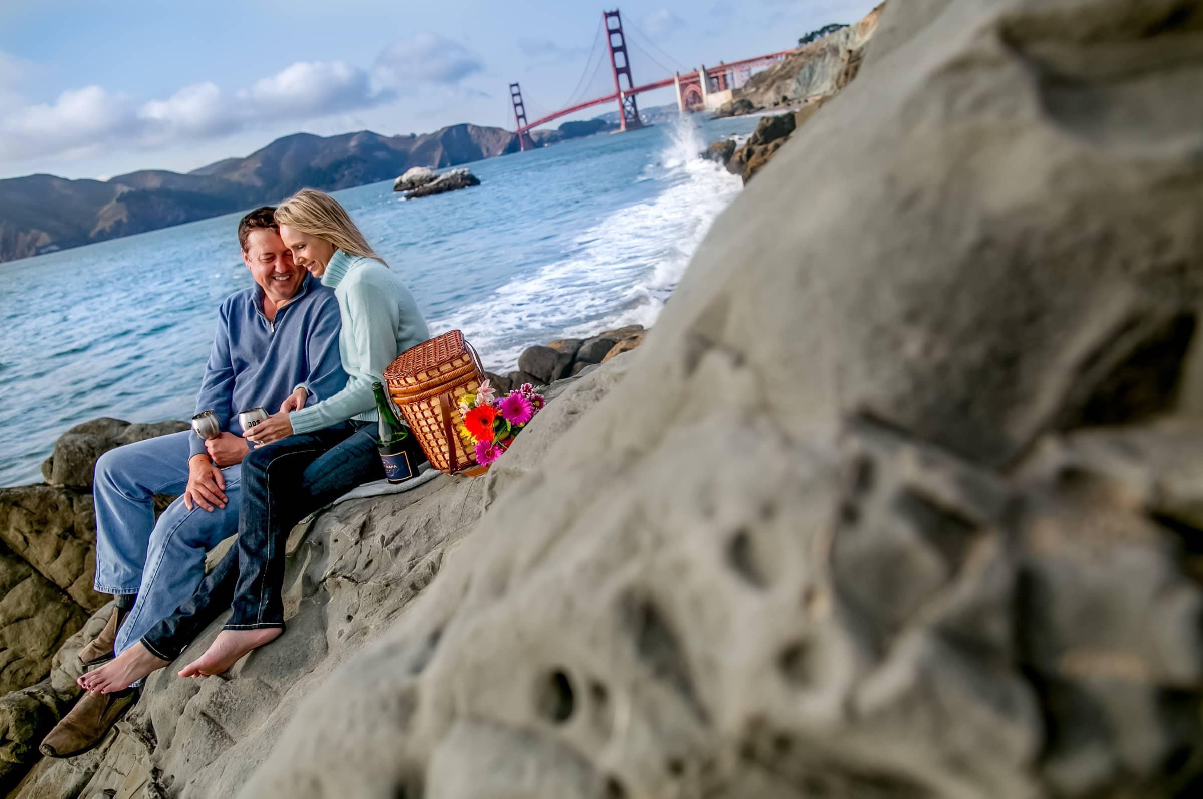 A couple enjoying a picnic for their Baker beach Engagement photos