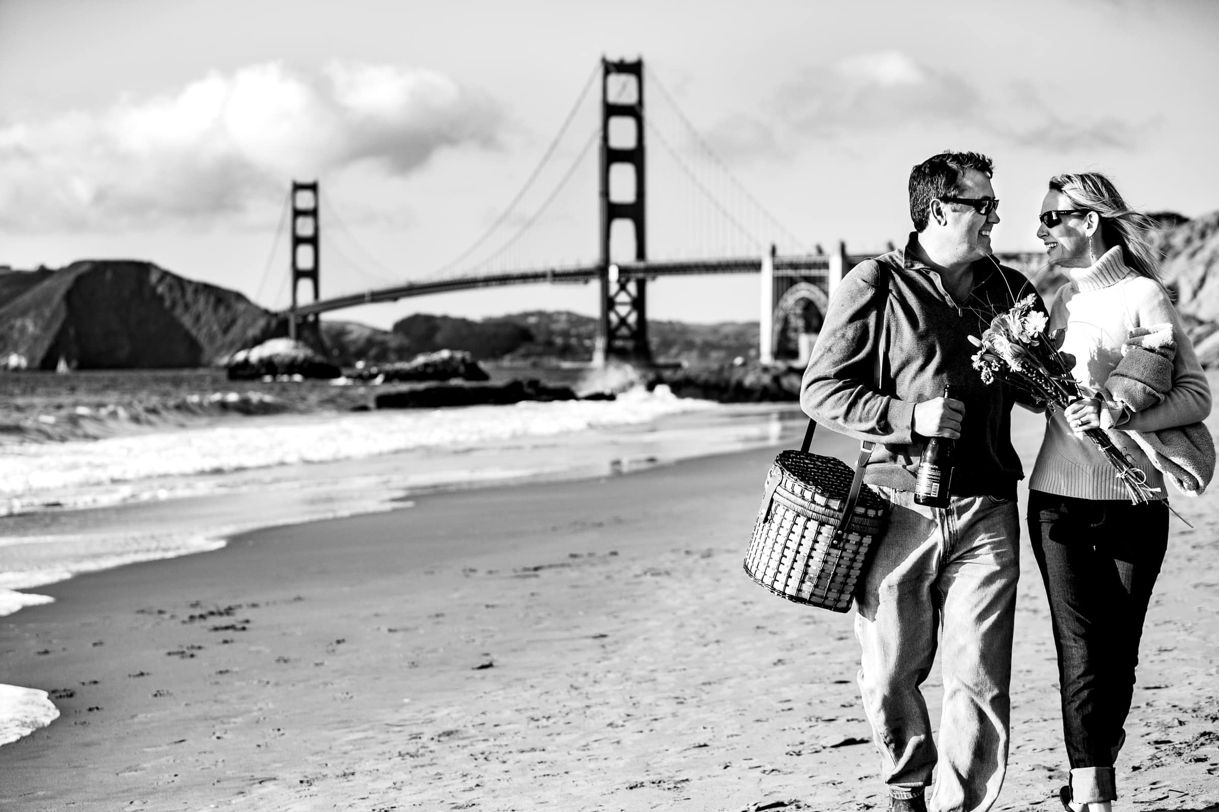 A couple walking on the sand for their Baker beach Engagement photos