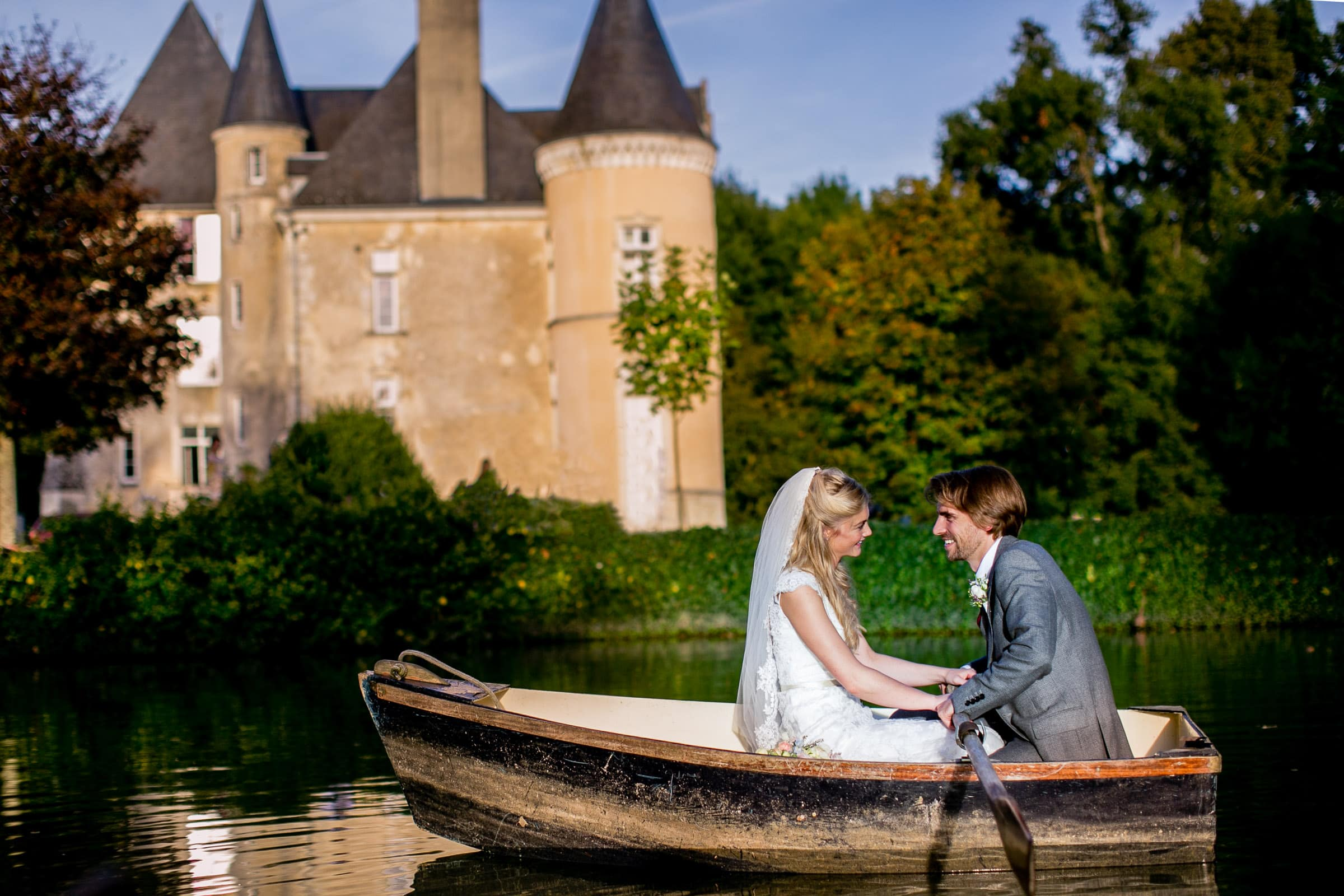 Bride and groom in a row boat during their French Chateau wedding in Normandy, France