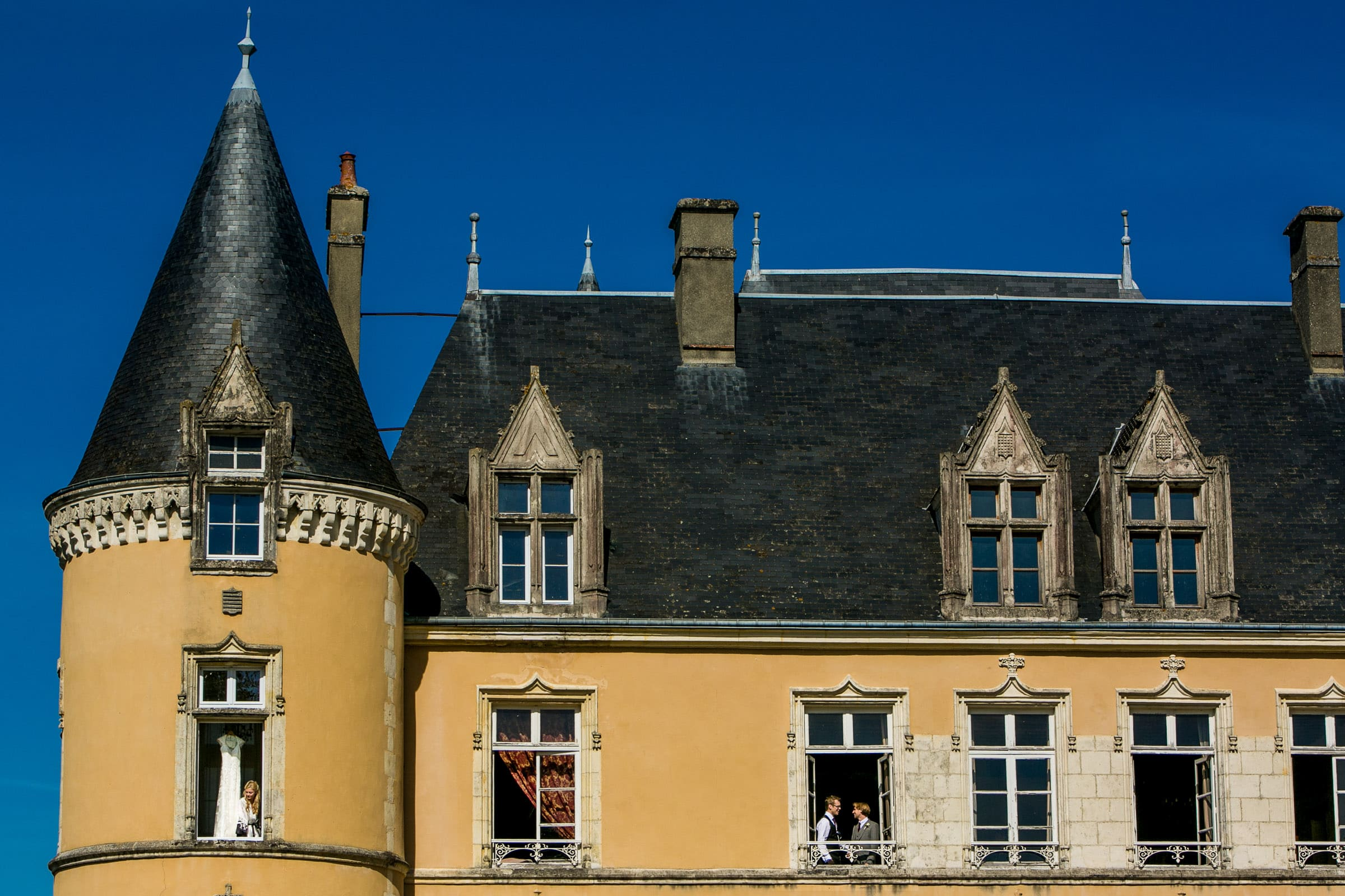 Bride and groom getting ready through windows during their French Chateau wedding in Normandy, France