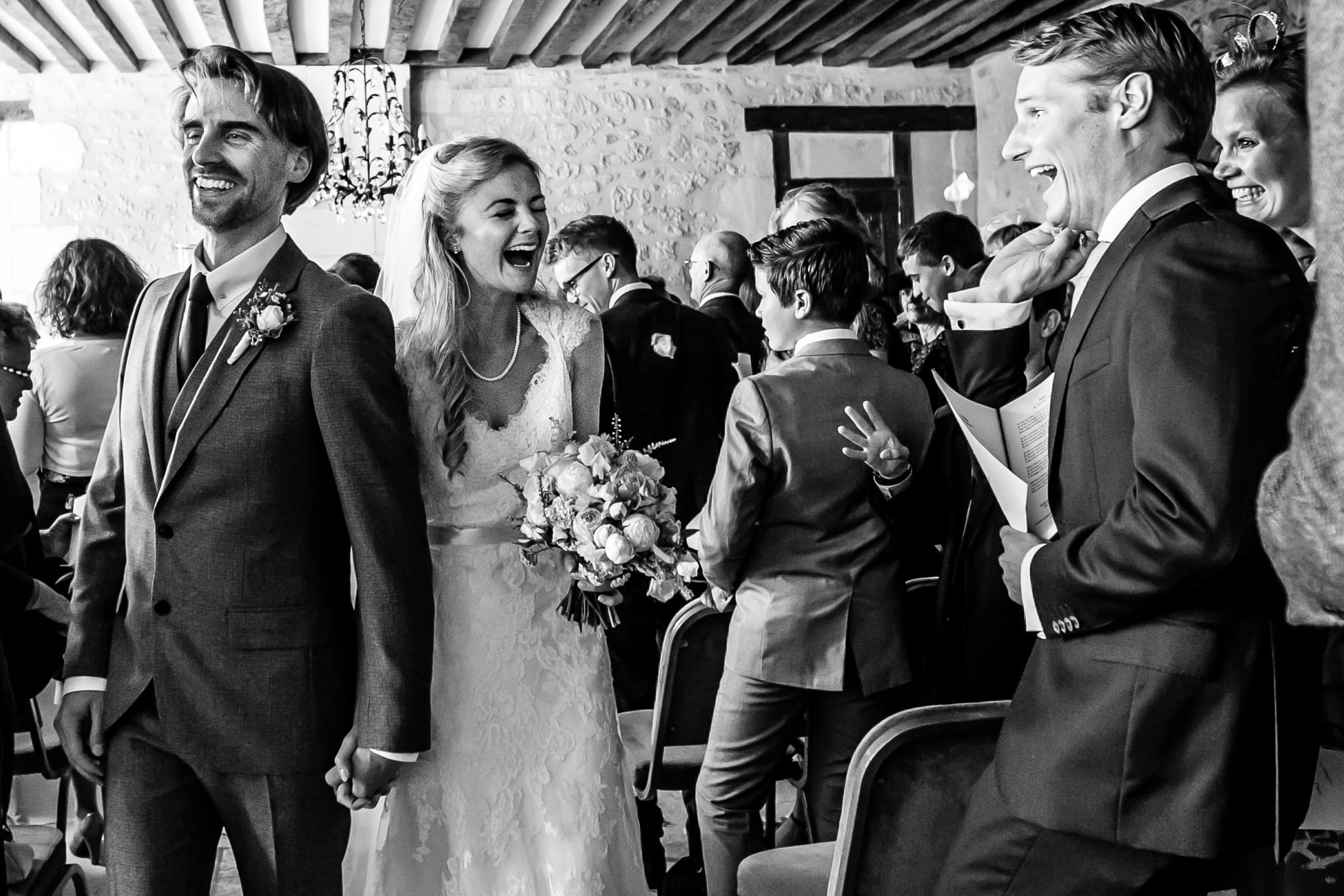 Bride and groom ecstatic excitement exiting their French Chateau wedding ceremony in Normandy France