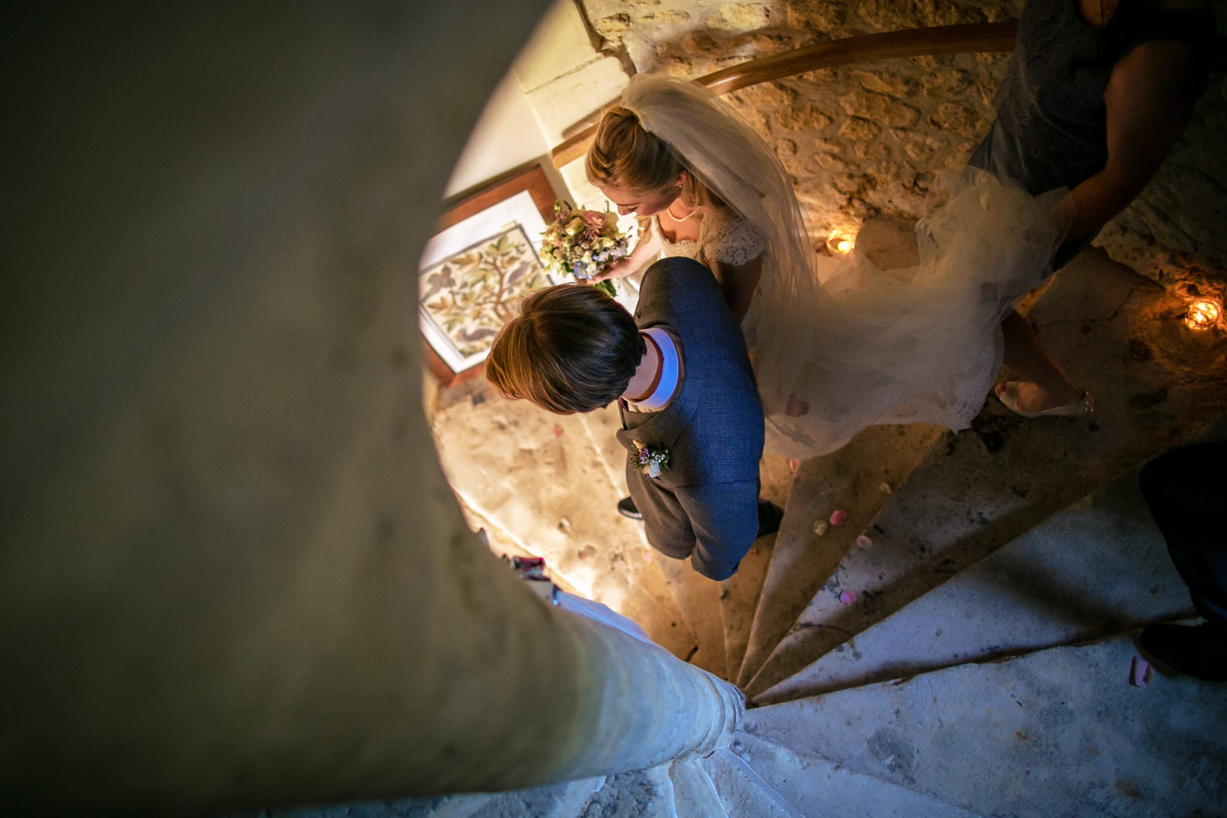Bride and groom exiting down a stone spiral staircase during a French Chateau wedding in Normandy, France