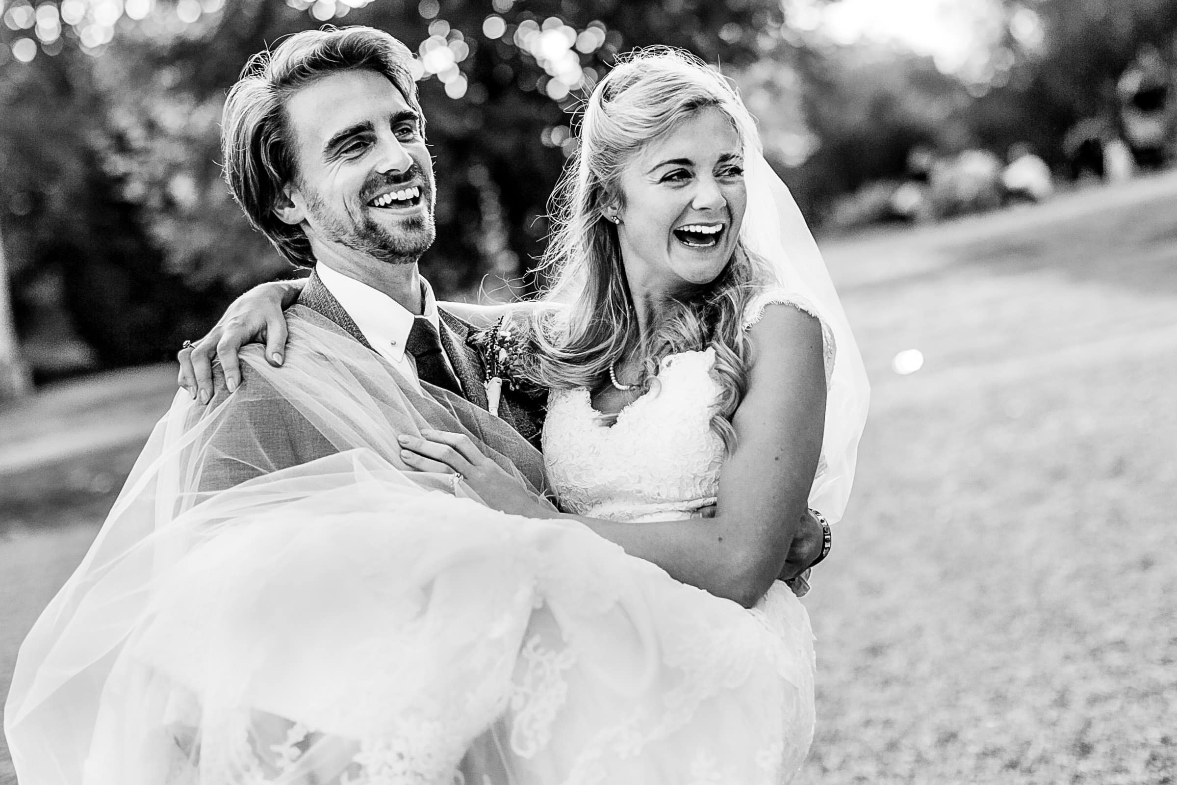Happy groom carrying a happy bride during a French Chateau wedding in Normandy, France