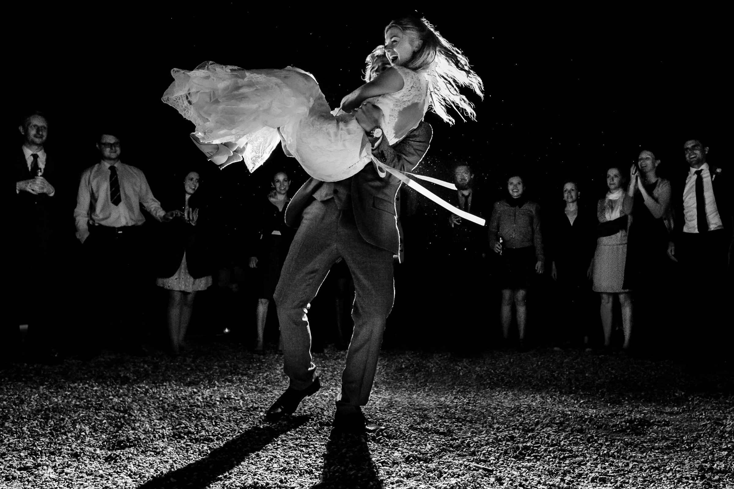 Groom swinging bride in the air dancing during a French Chateau wedding in Normandy, France