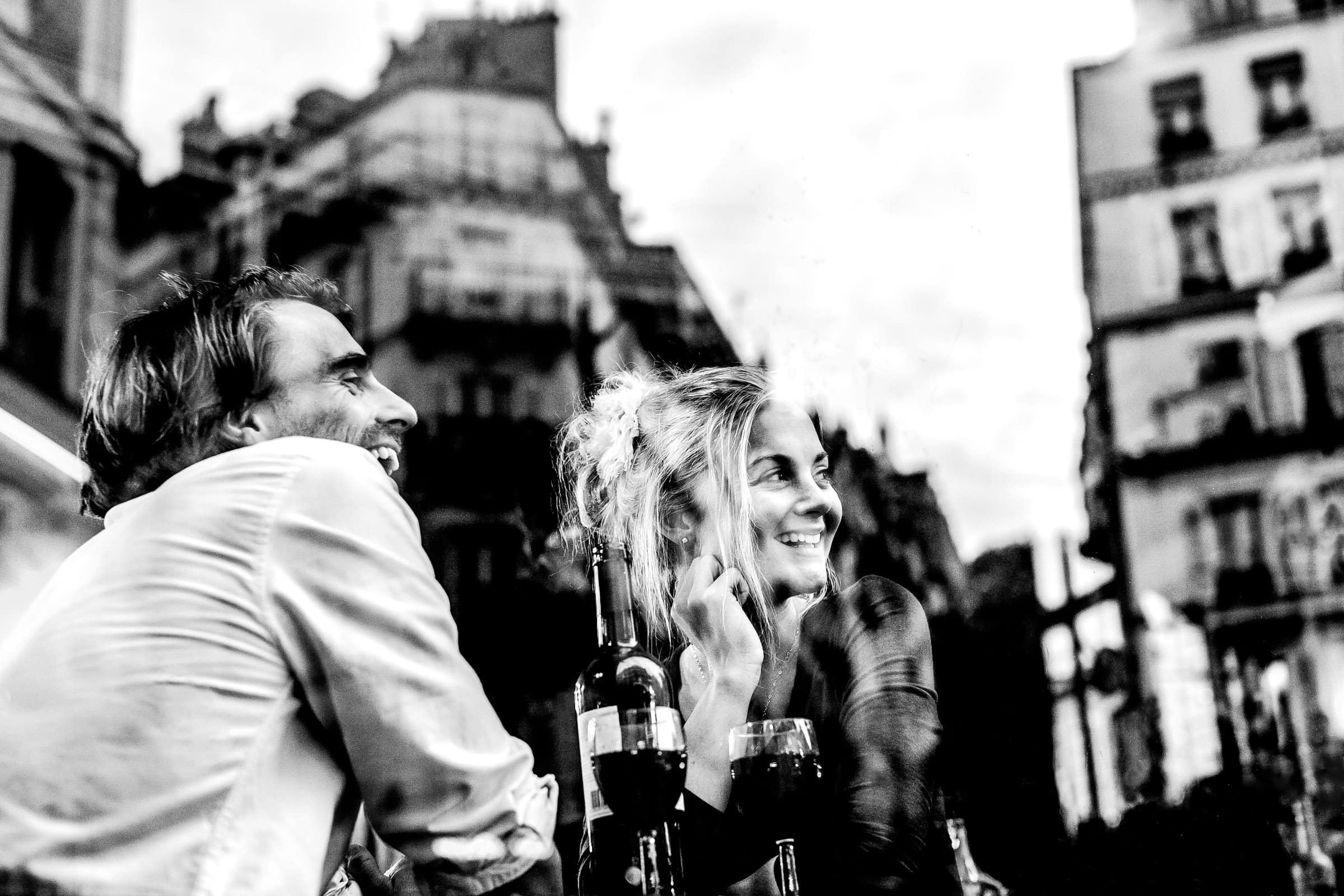 A peaceful moment of connection during Faye and David's Montmartre Paris Engagement date at Vins & Liqueurs with wine while looking out the window through reflections